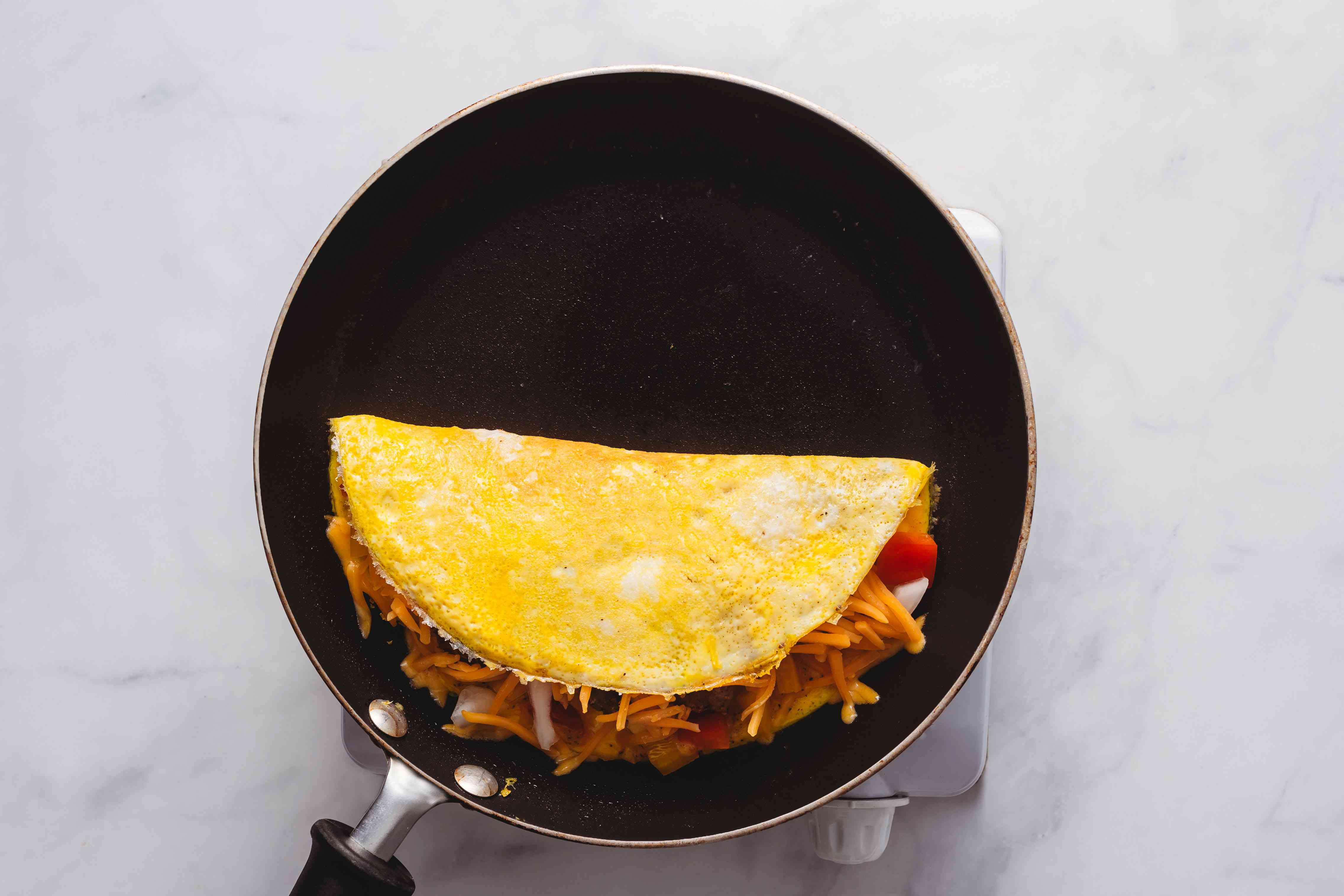 omelet folded over the filling in the skillet
