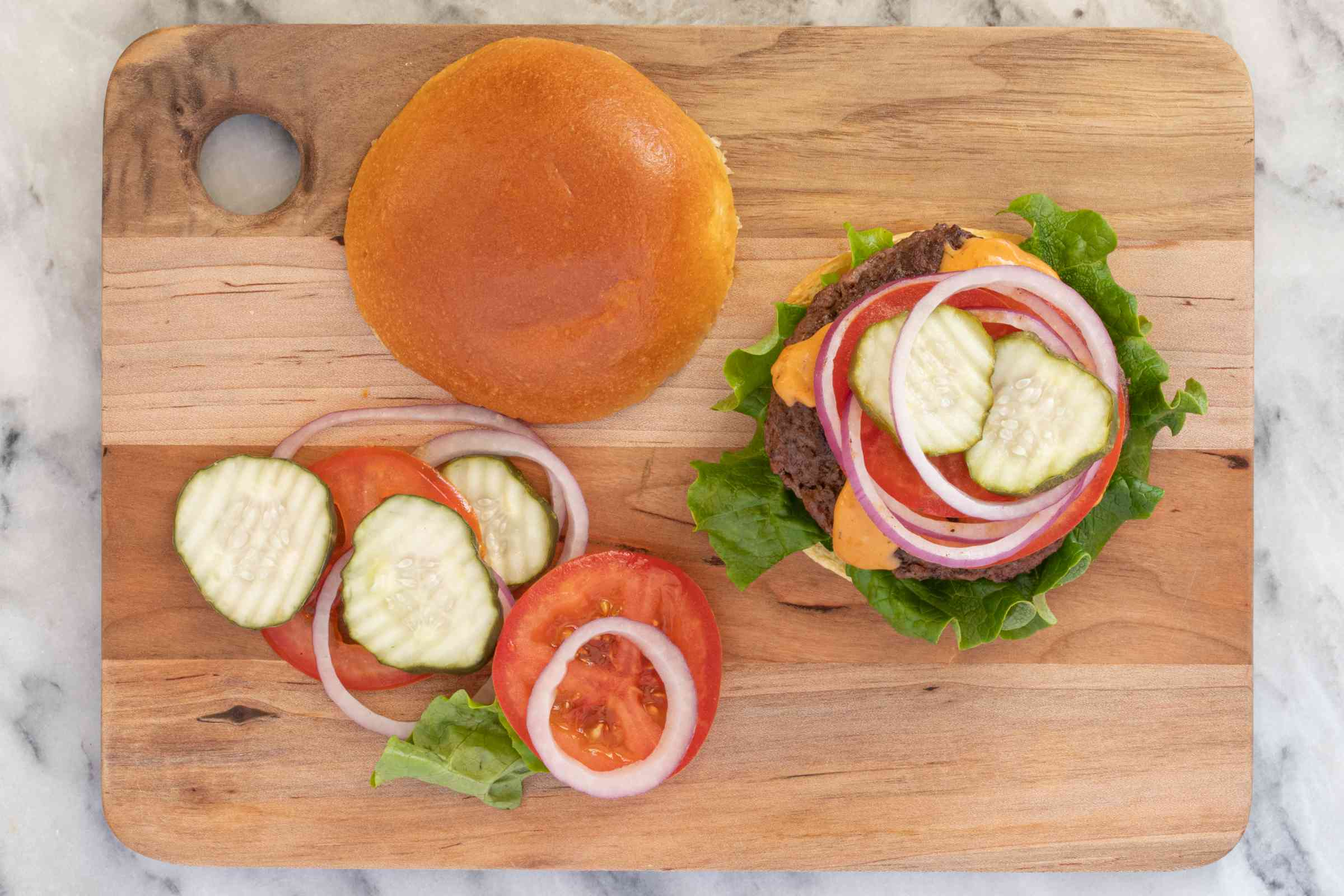 Assembly of one bison burger with bun and toppings.