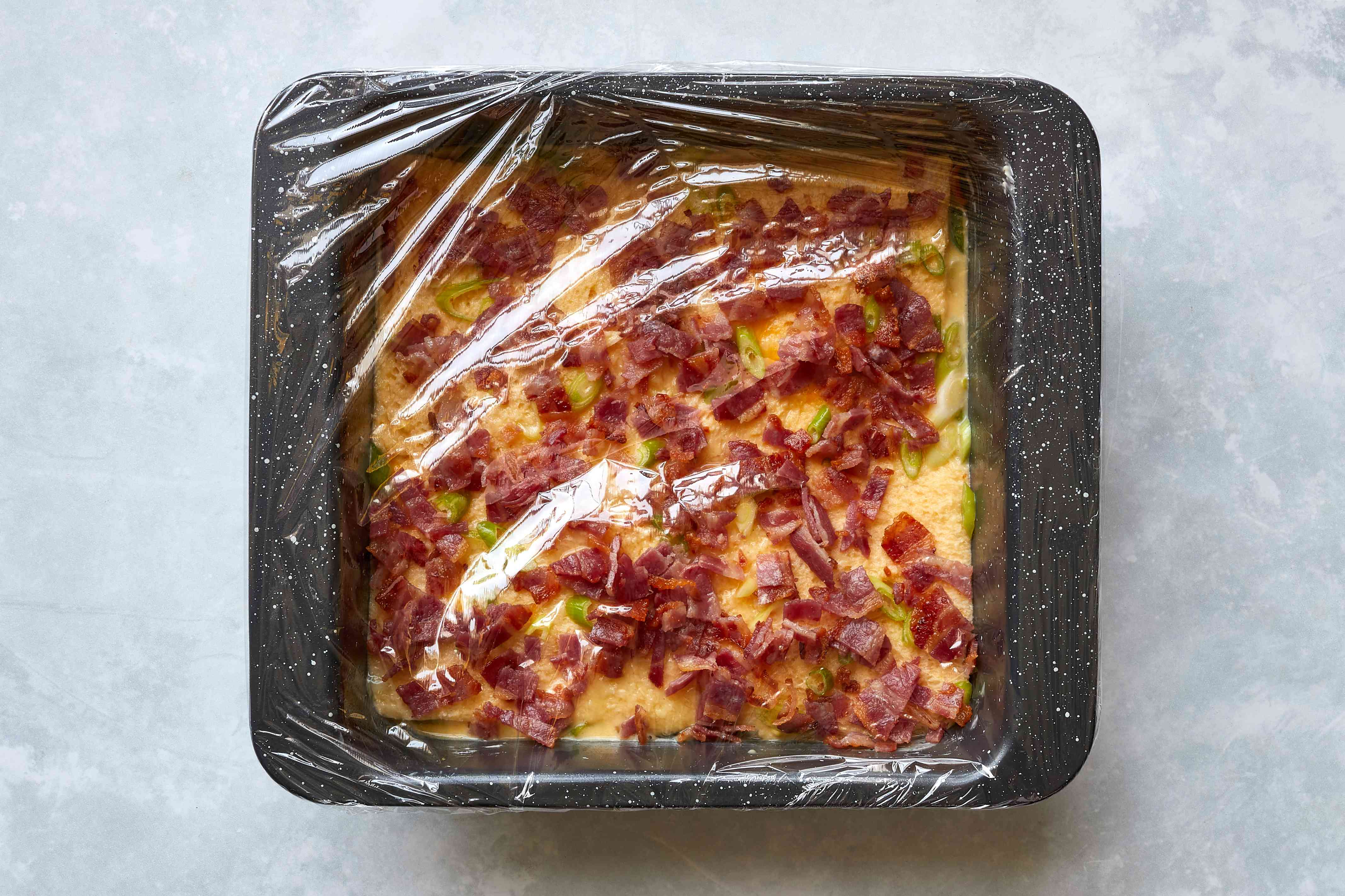 plastic wrap over the baking dish with bacon and eggs casserole