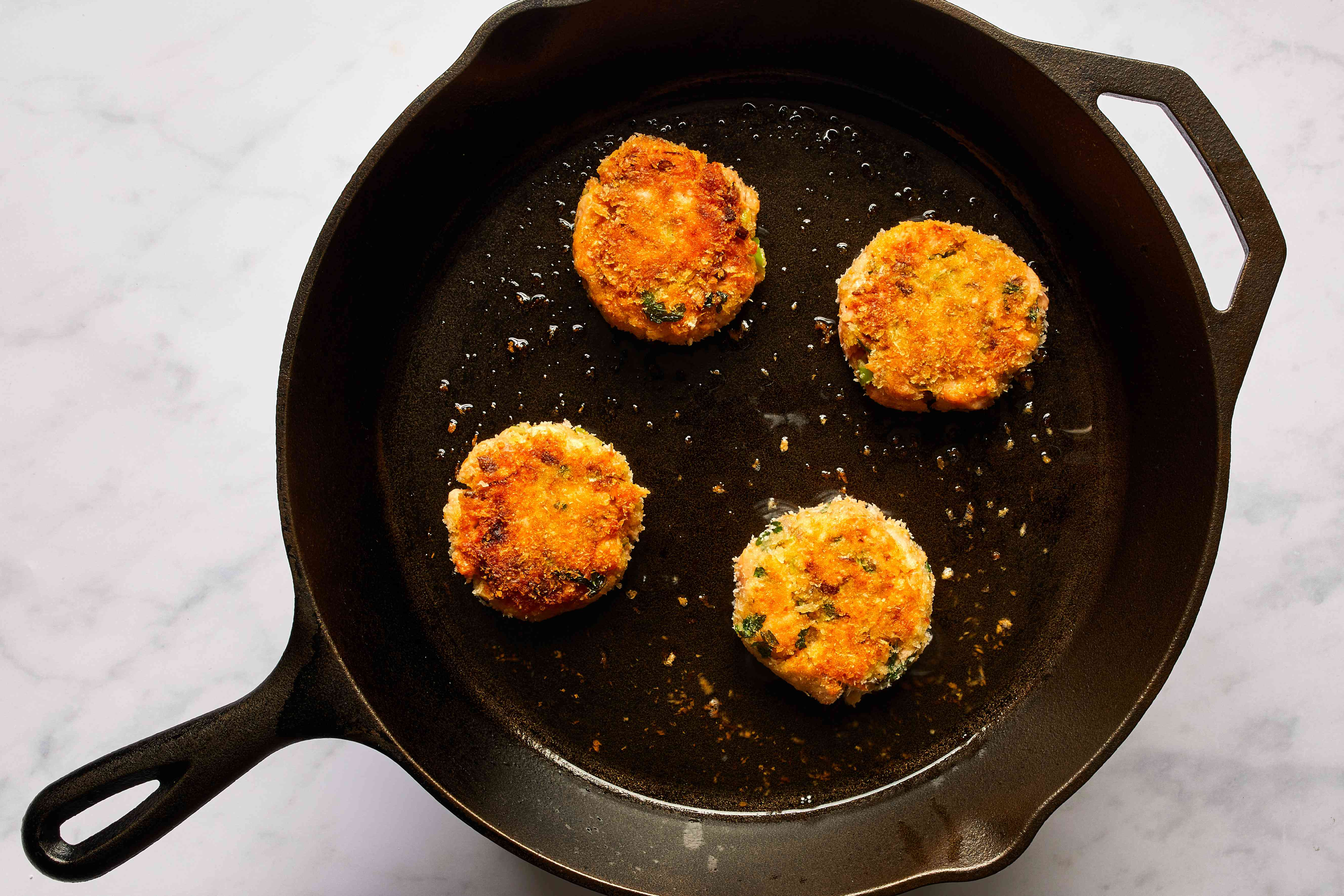 Panko-crusted salmon cakes in a cast-iron pan