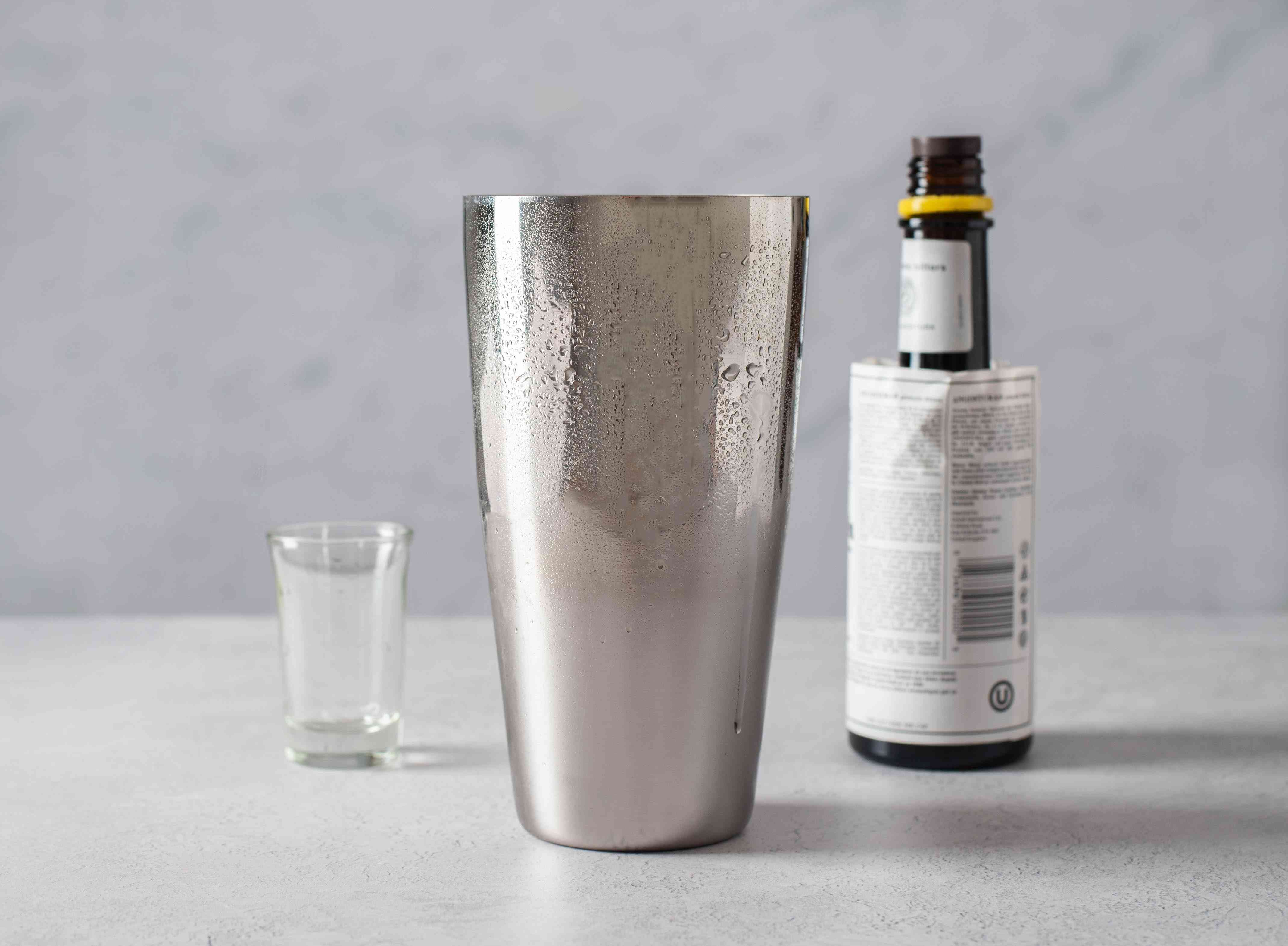 In a cocktail shaker filled with ice cubes, combine the gin and bitters