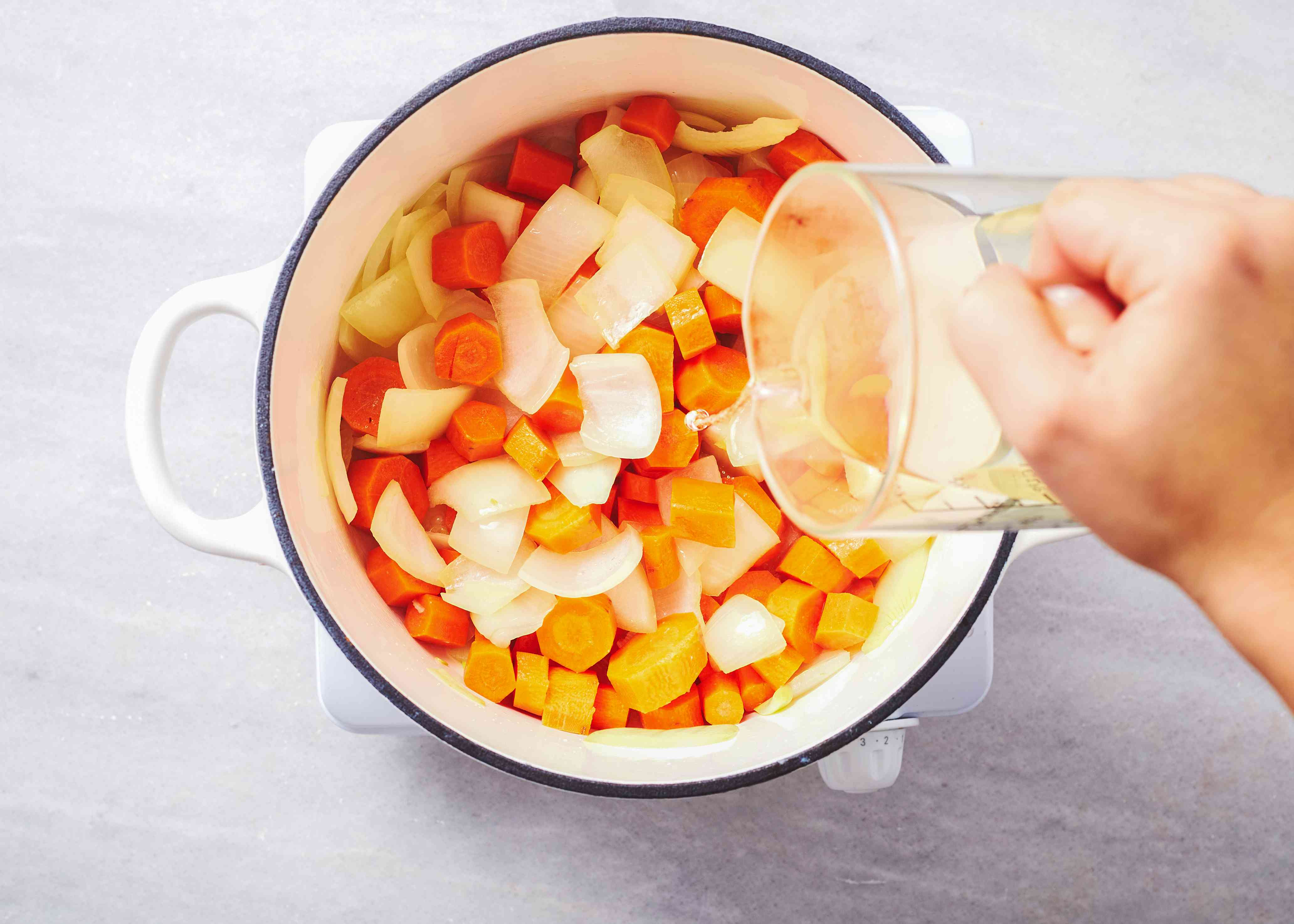 add wine to the onions and carrots to the pot