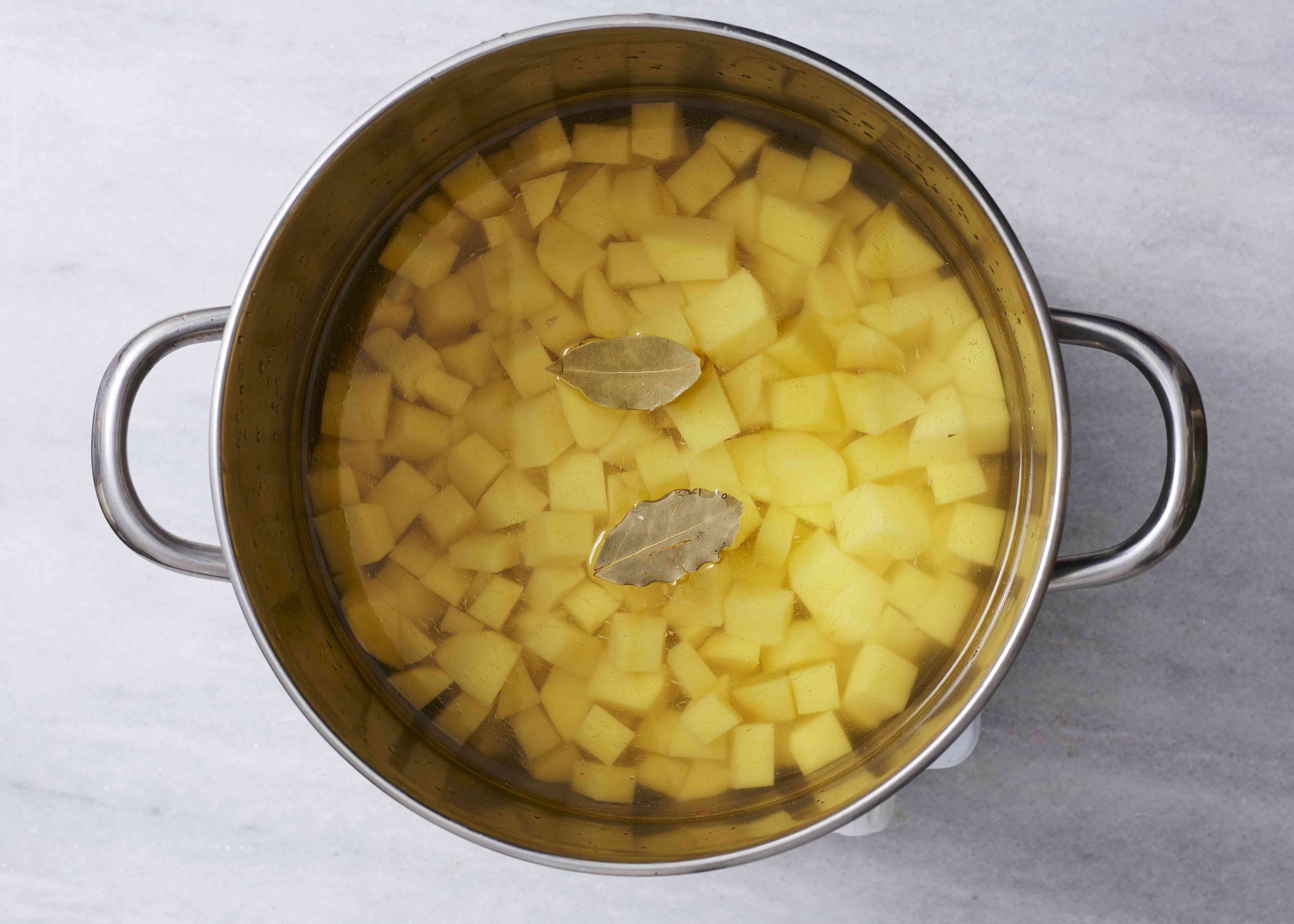 boil the potatoes and the bay leaves in salted water