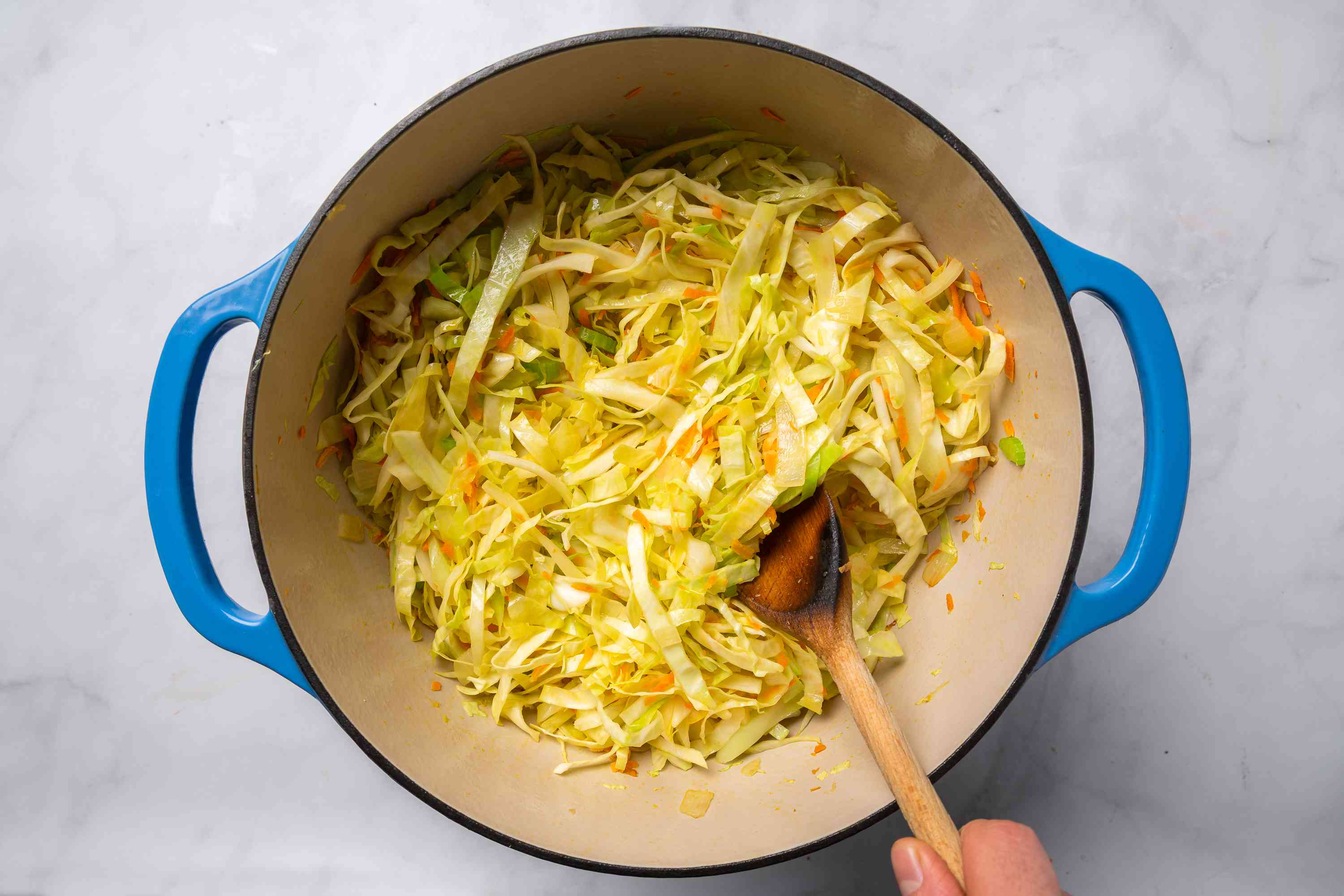shredded cabbage, grated carrot, and chopped celery added to the onions in the Dutch oven