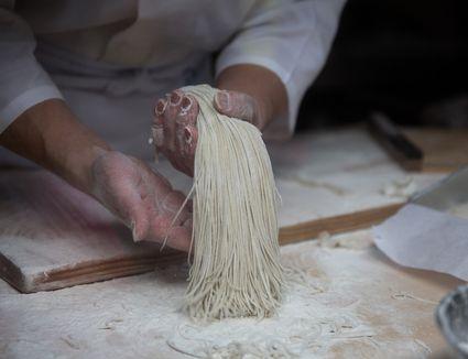hands making noodles