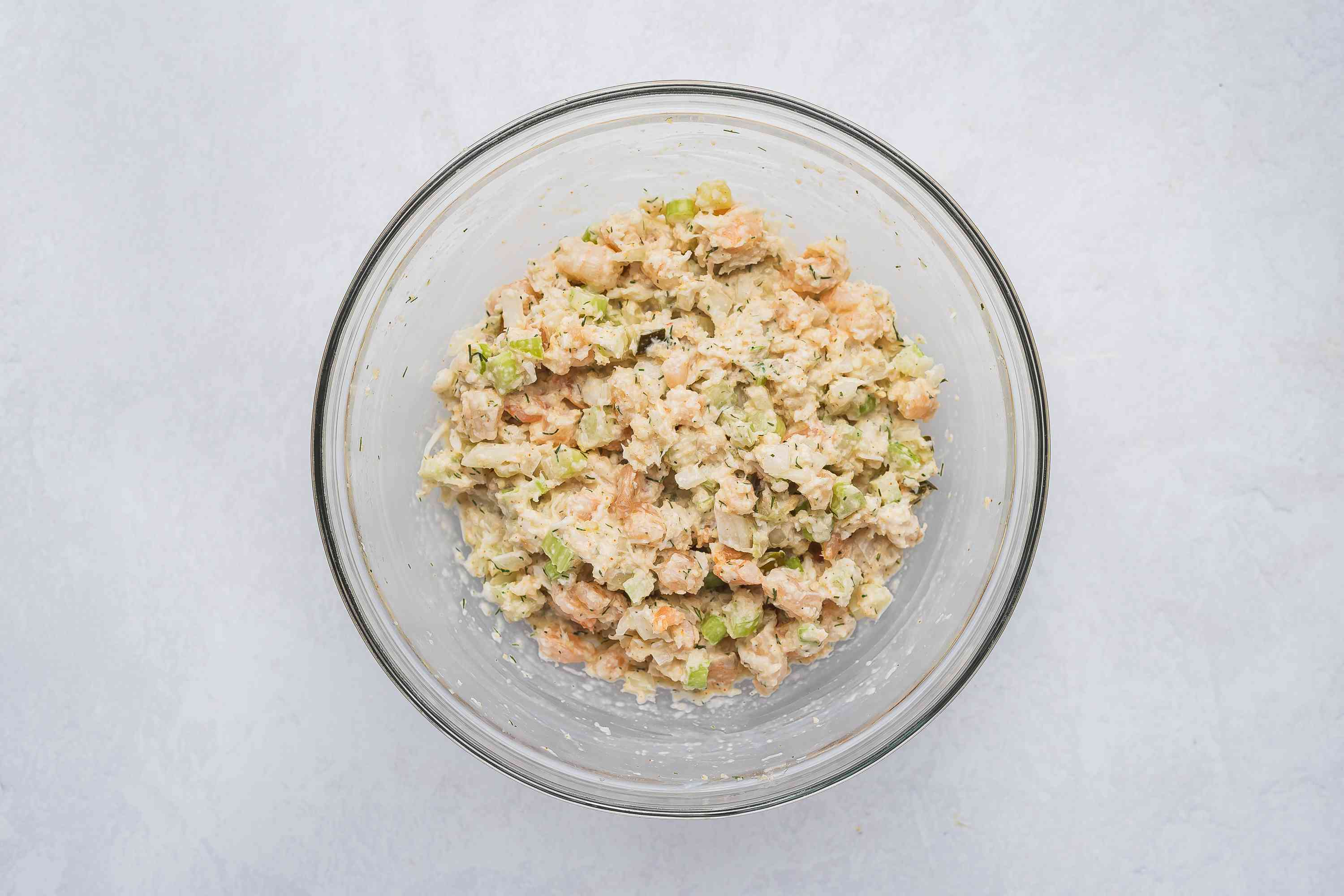Mayo added to crab and shrimp mixture in a bowl