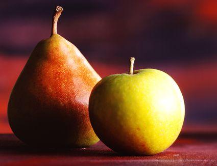 An apple and a pear on a table