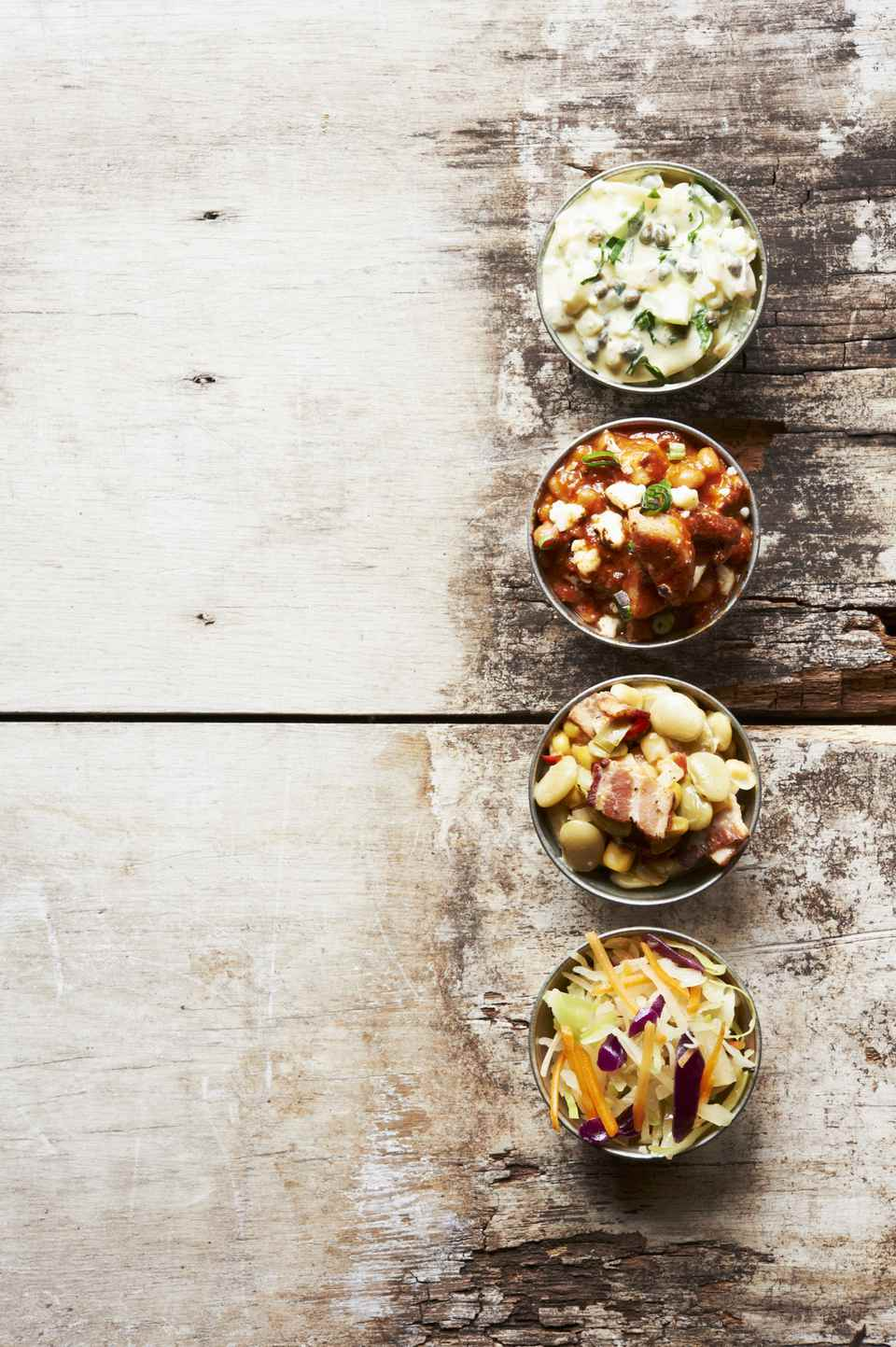 Barbecue Side Dishes in Small Bowls on a Wooden Table, Pork and Beans, Potato Salad, Cole Slaw and Succotash