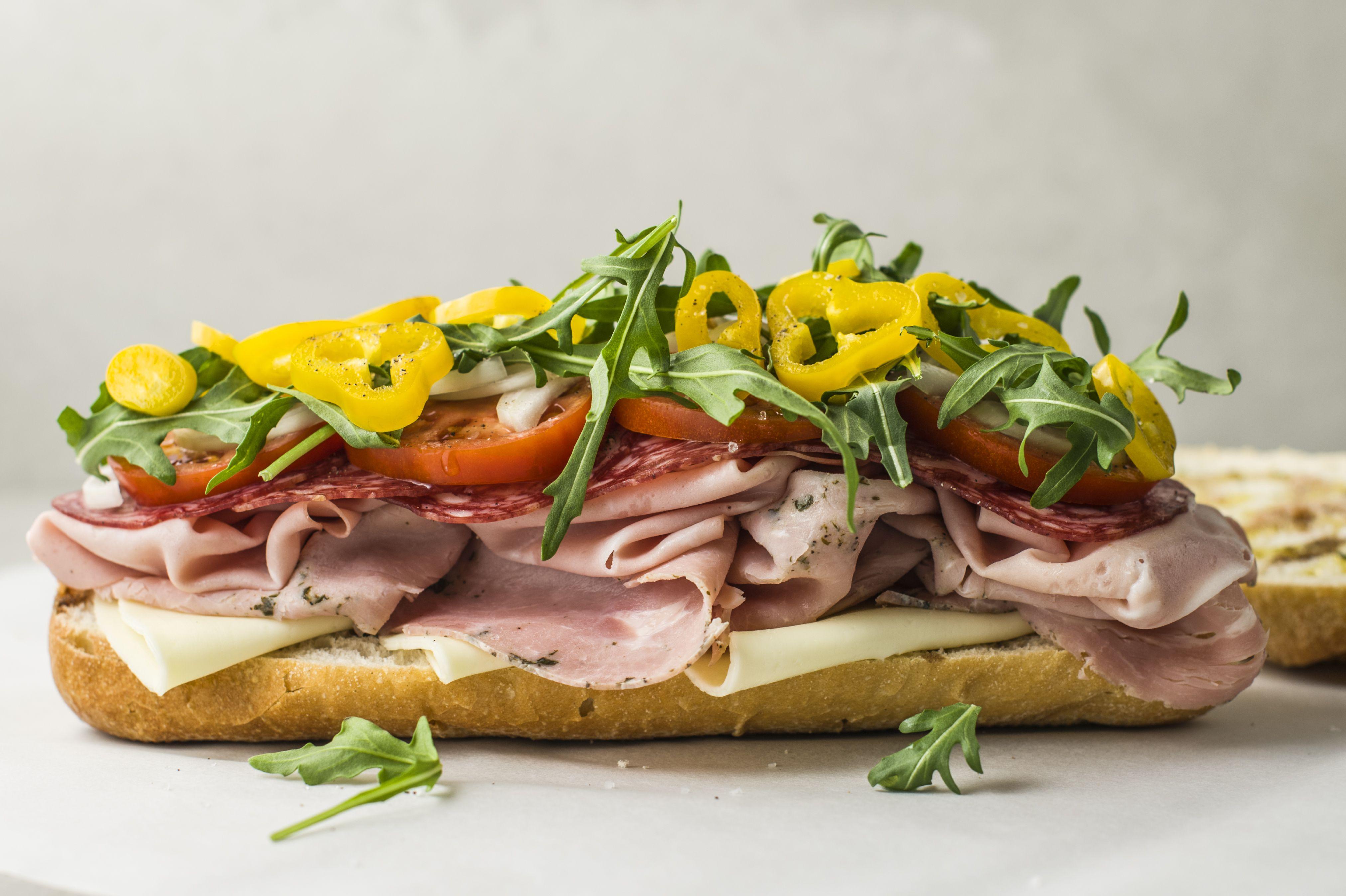 add provolone, ham, mortadella, soppressata, tomatoes, onion, lettuce, banana peppers, salt, and pepper