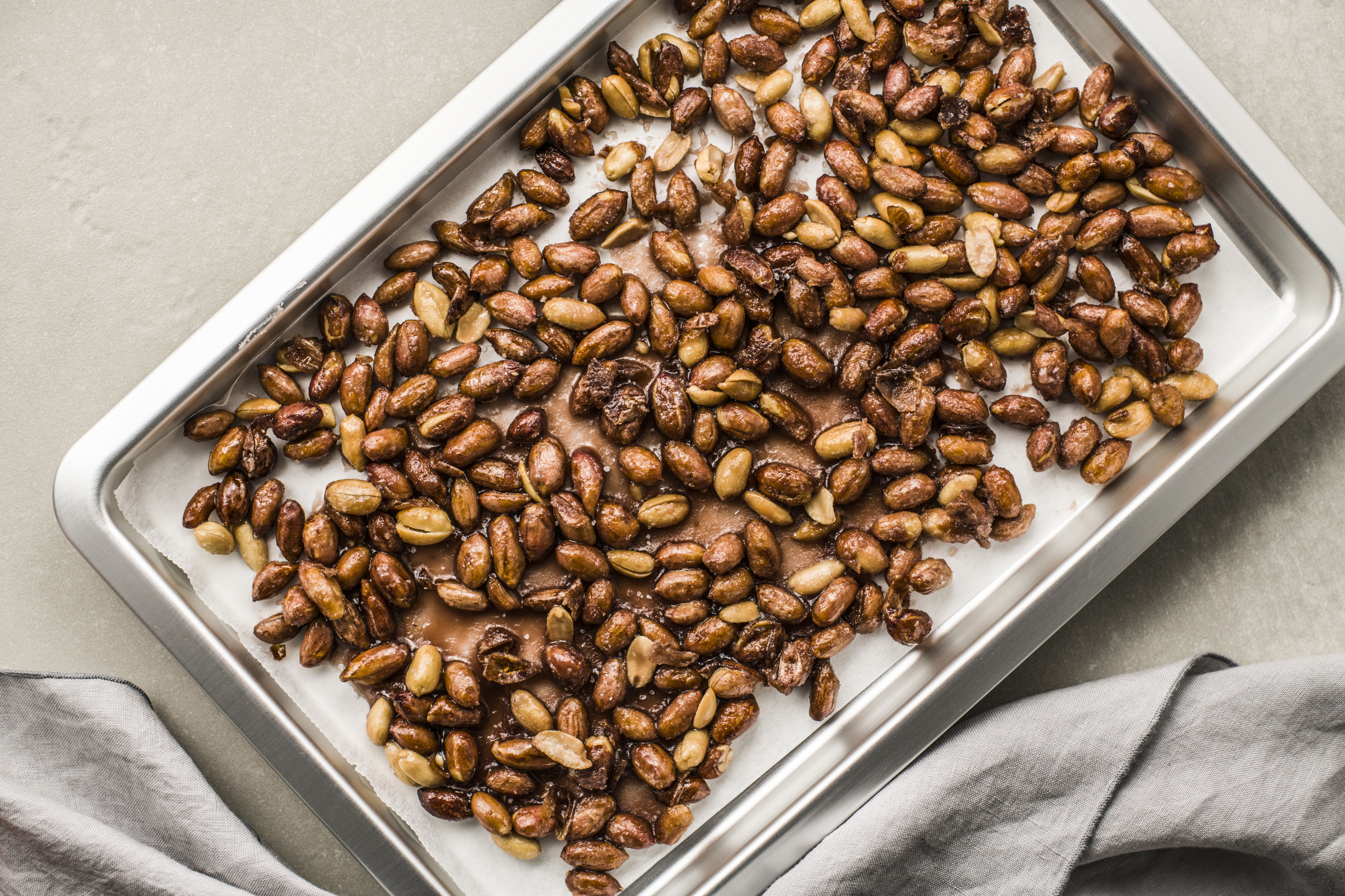 Spread peanuts onto prepared pan to cool