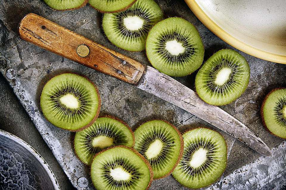 Sliced fresh kiwifruit on a plate with a knife