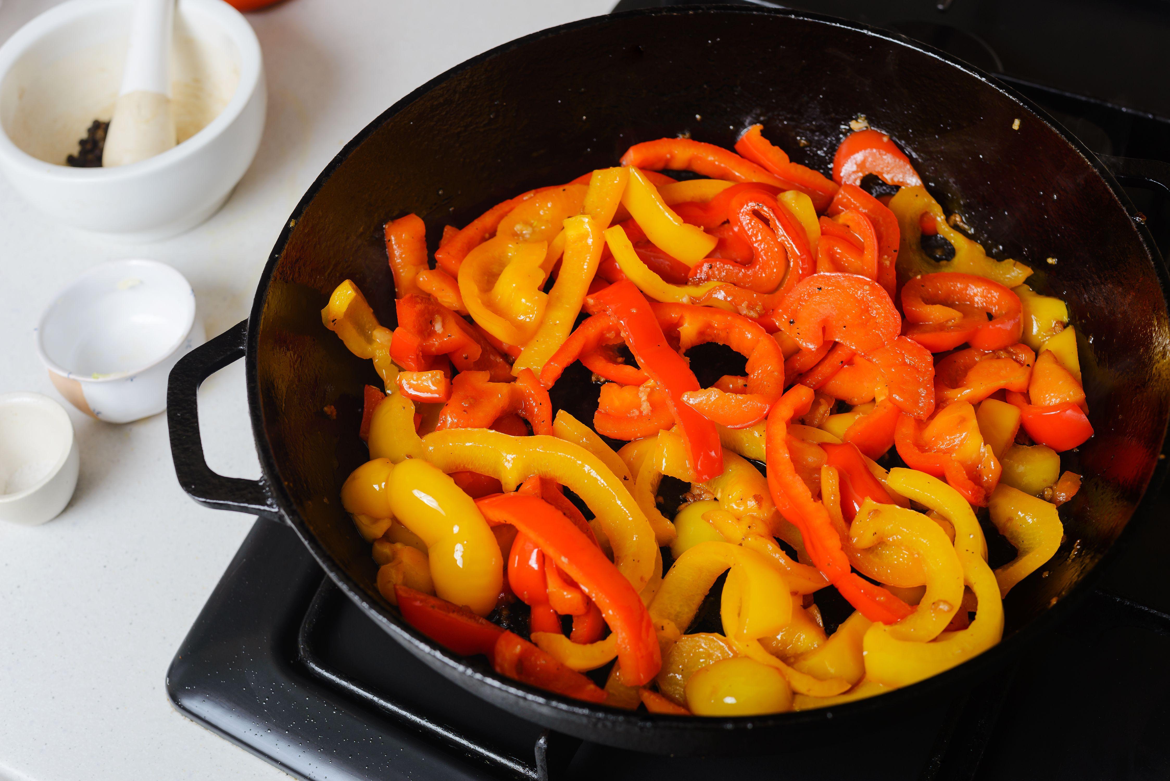 Pepper strips sautéing with garlic, salt, and pepper