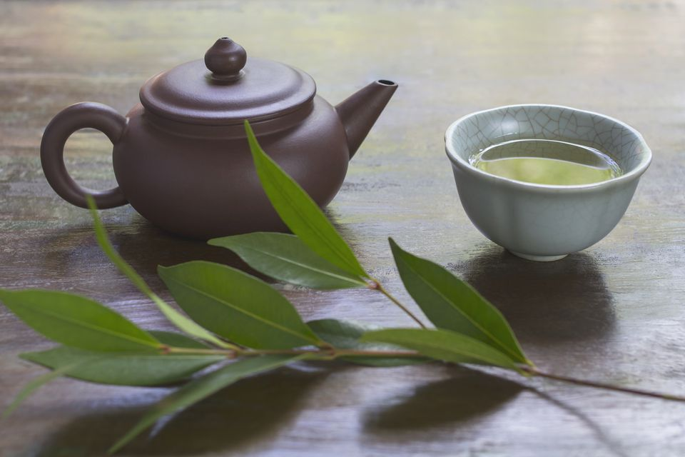 Herbal tea in cup with teapot and leaves on table