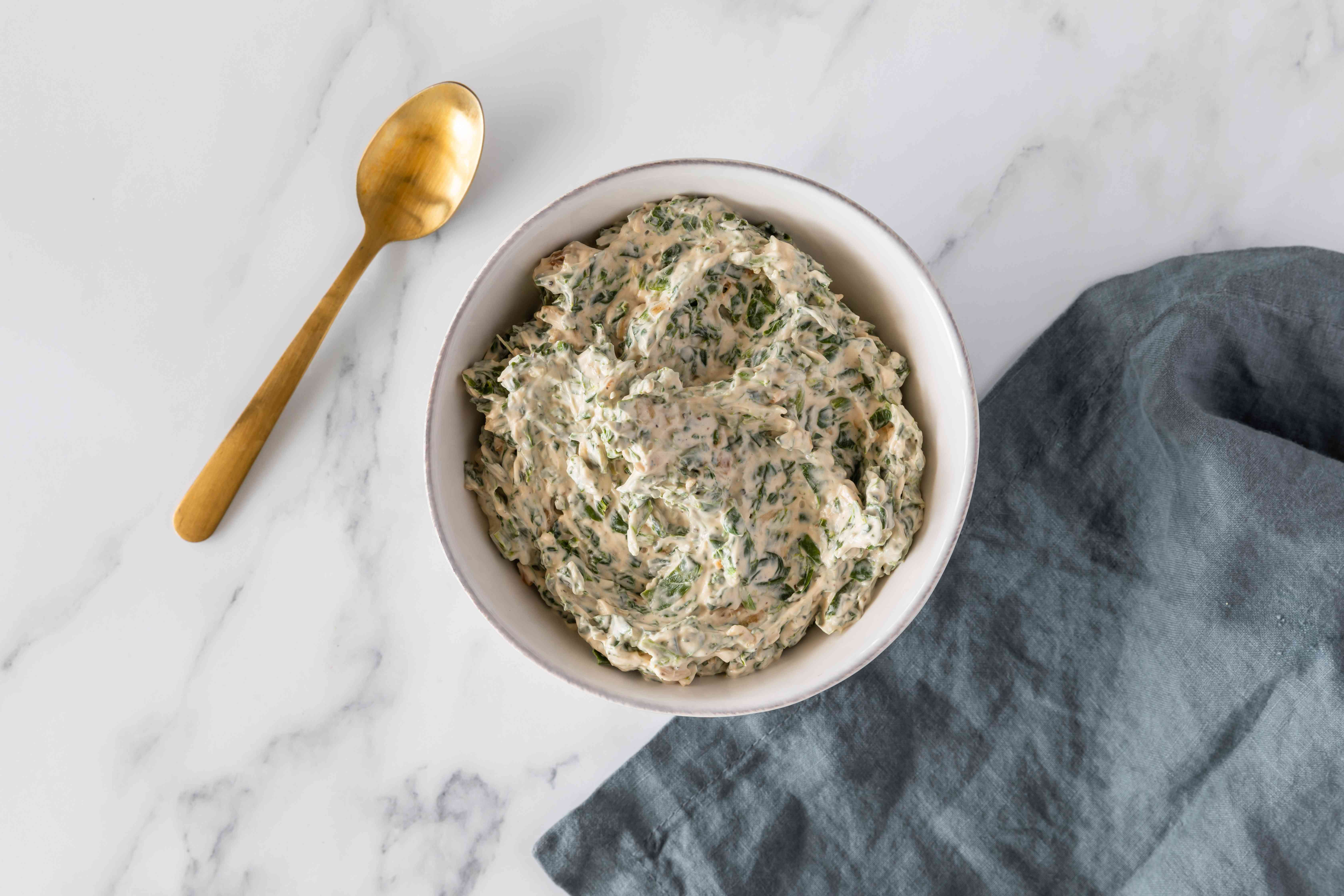 Spinach dip in bowl with gold spoon