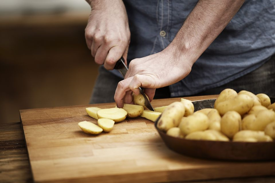 Man cutting potatoes in a kitchen