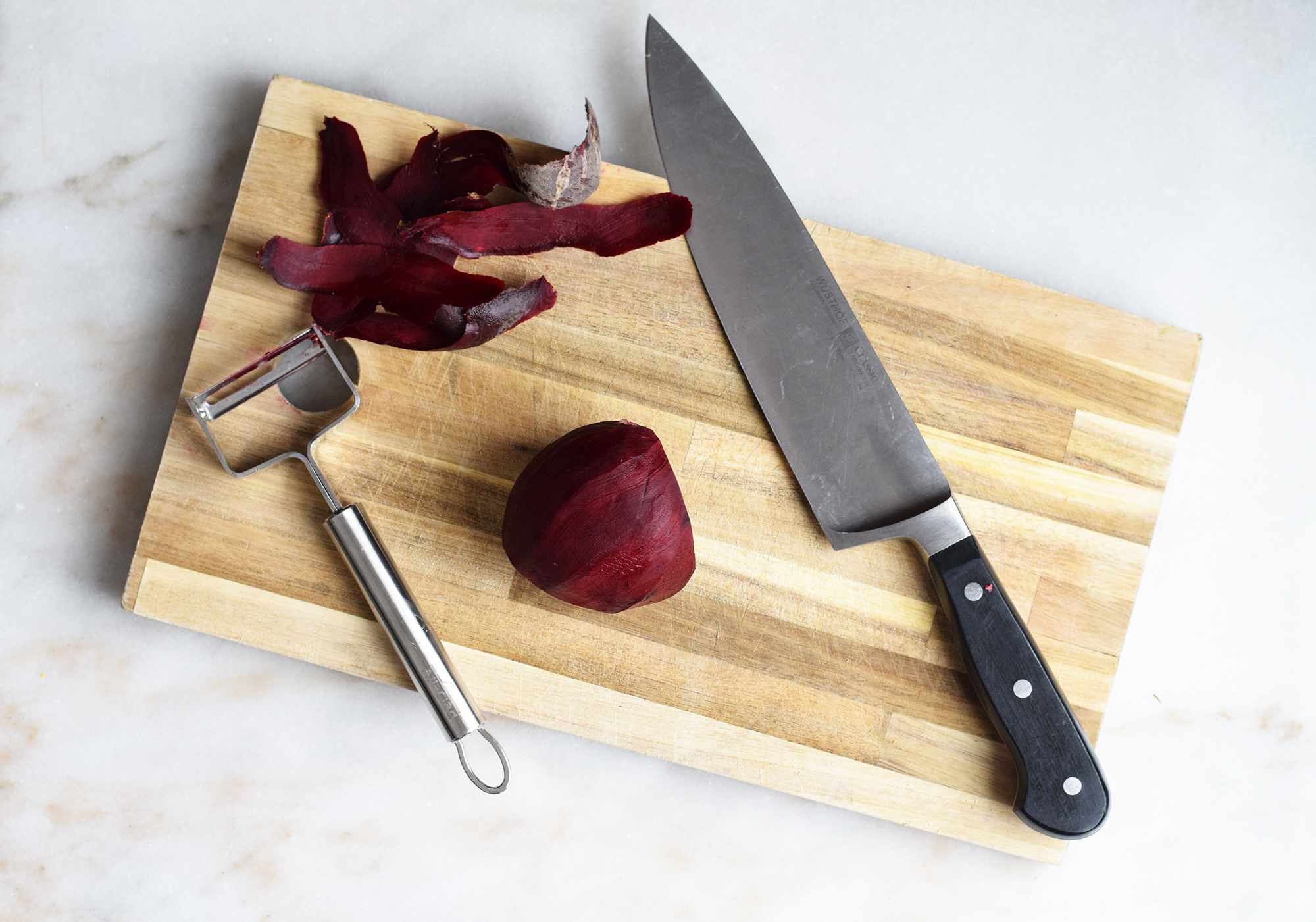 peeled raw beets on a cutting board