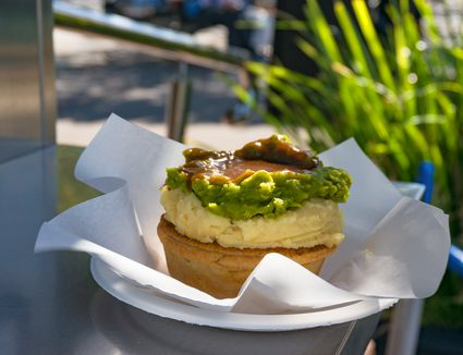 Australian individual meat pie with mashed potato topping, mushy peas, and gravy