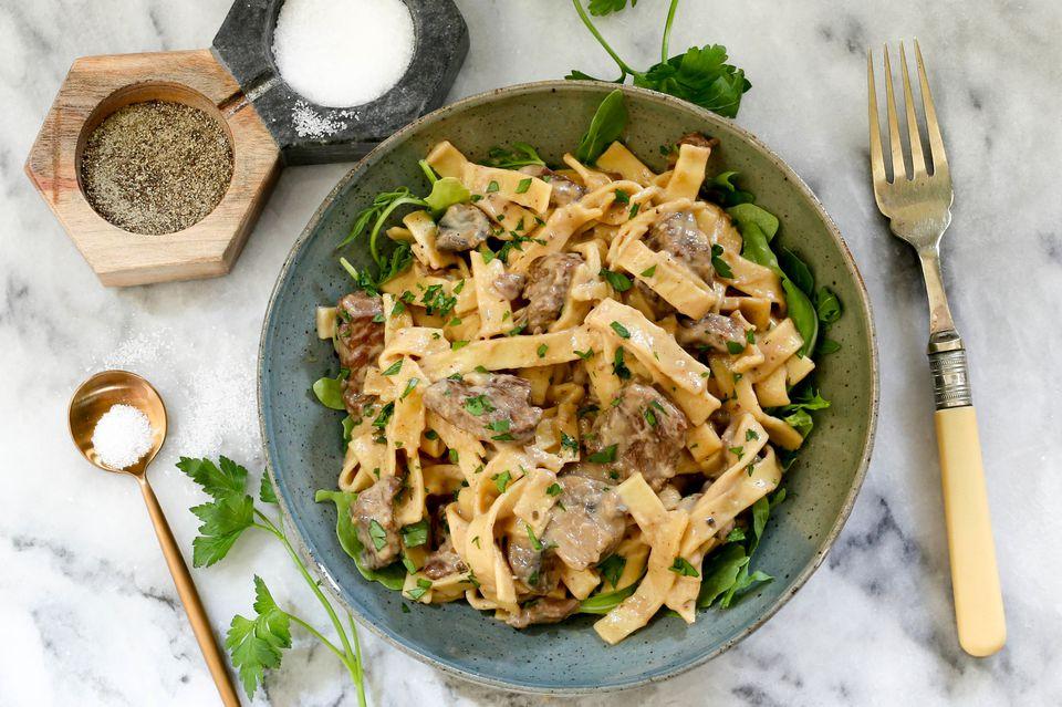 Serve the beef stroganoff with parsley garnish.