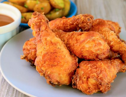 Crispy fried chicken drumsticks piled on a plate