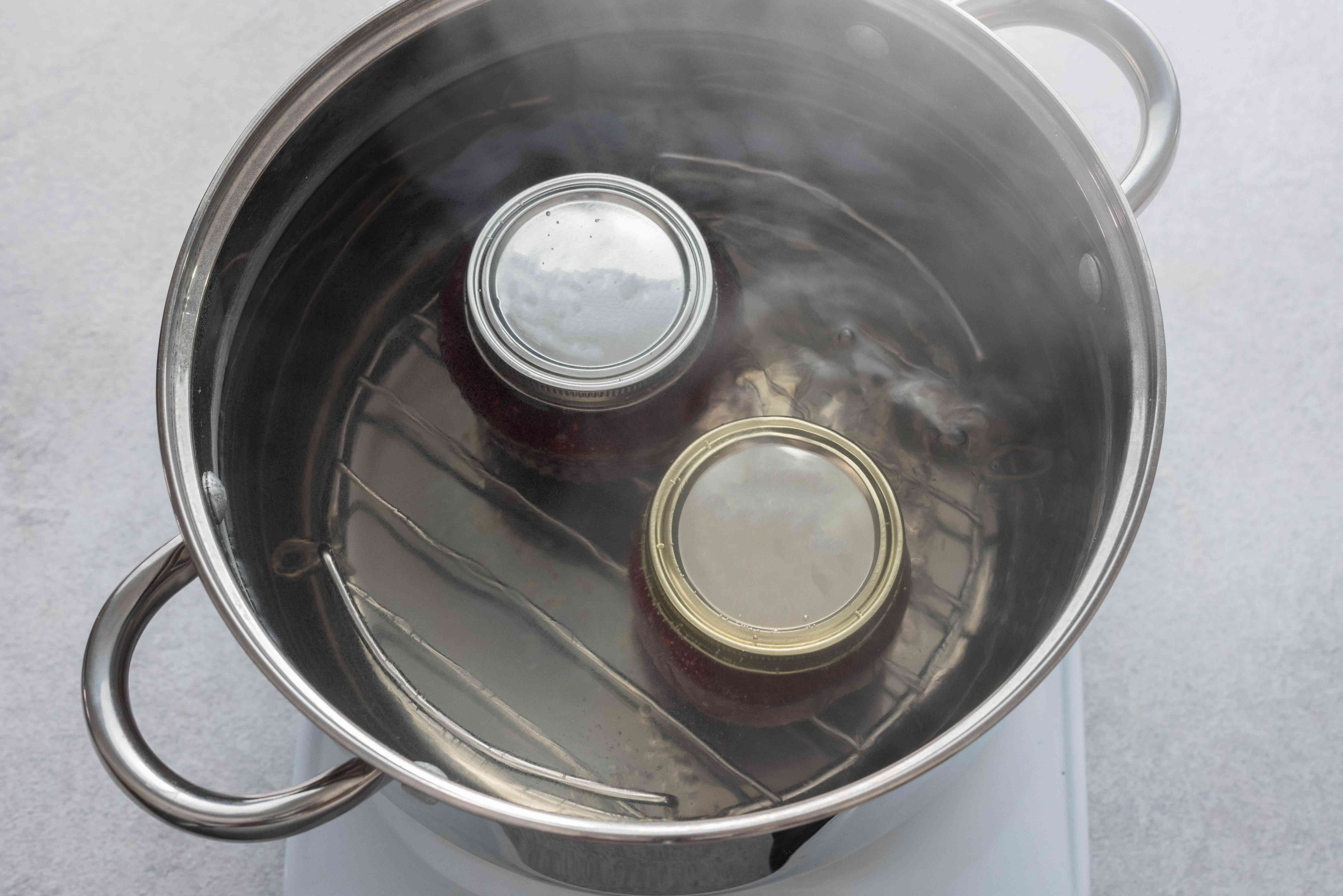 Jars with raspberry jam processing in a boiling water bath