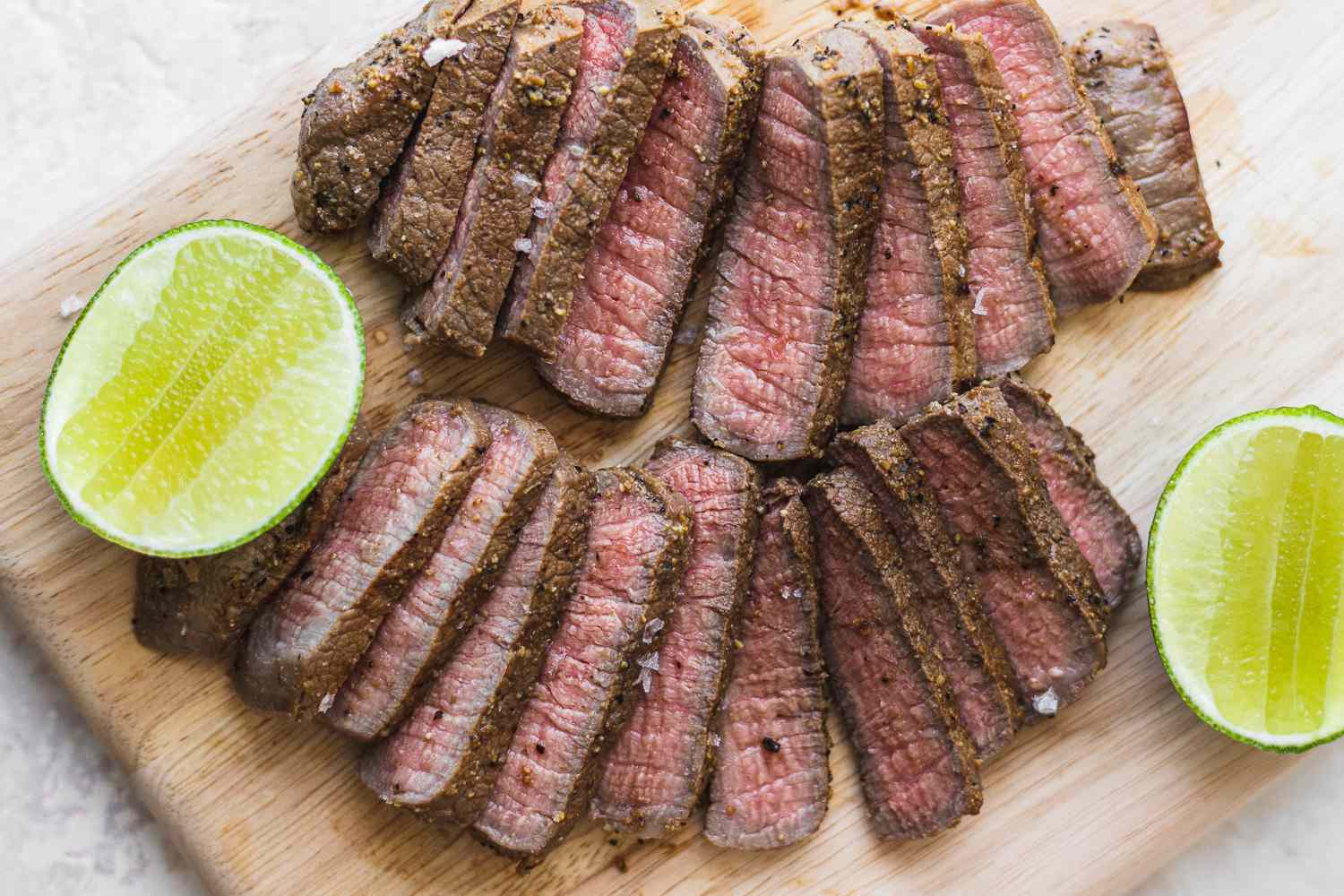 Spiced Lime-Marinated Eye of Round Steaks, sliced and garnished with limes