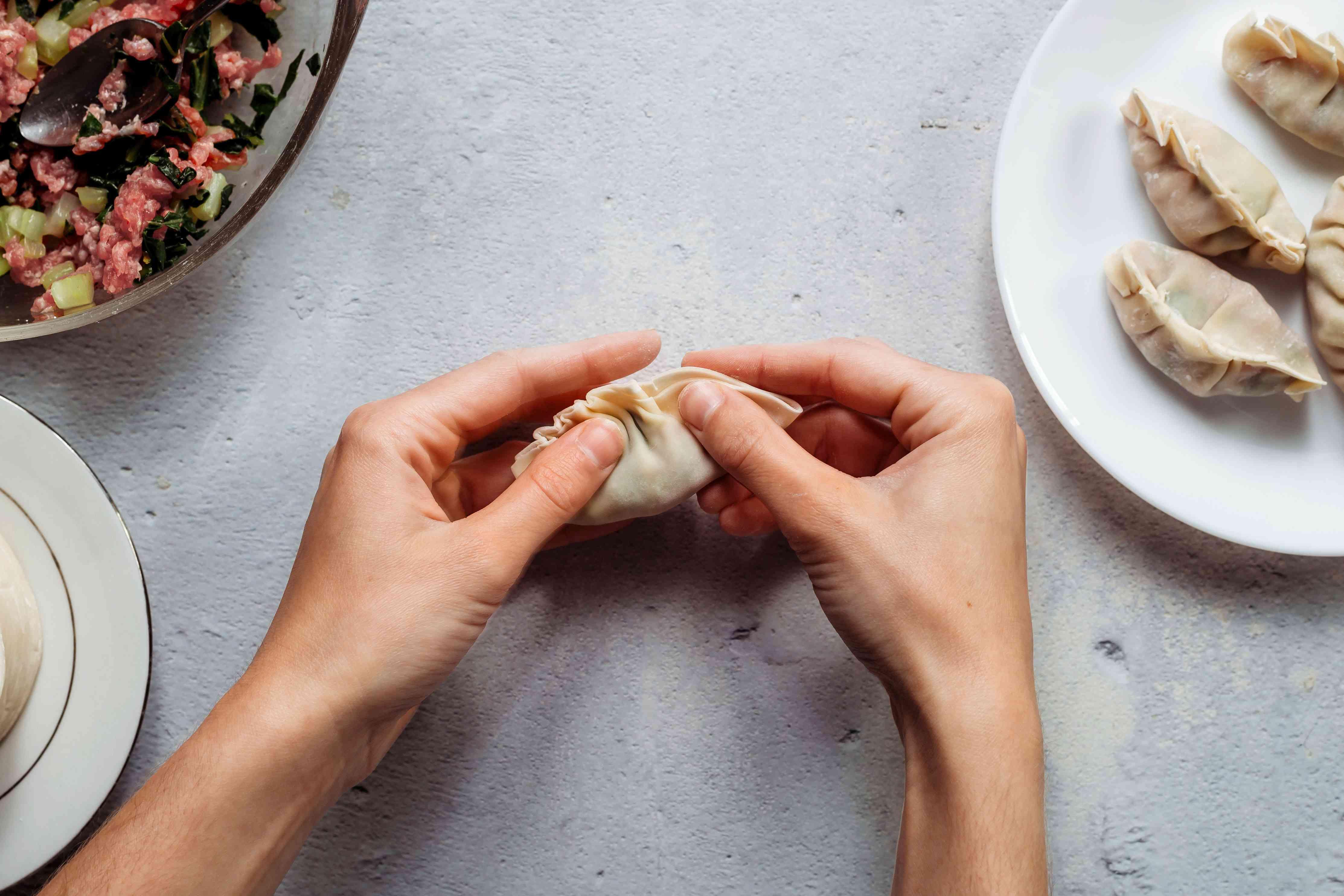 Hands sealing potsticker