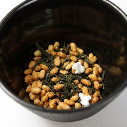 Genmaicha, a Japanese tea blend made of green tea and toasted and/or puffed rice in a black bowl.