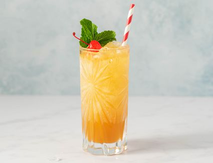 Yellow bird cocktail garnished with cherry and mint