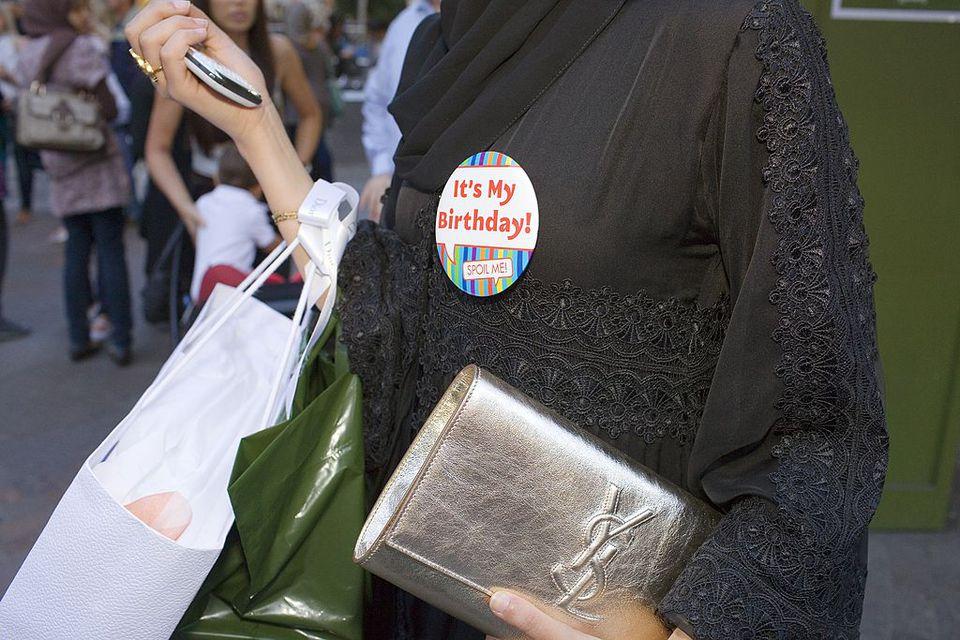 "An arab woman wearing an ""it's my birthday!"" pin"