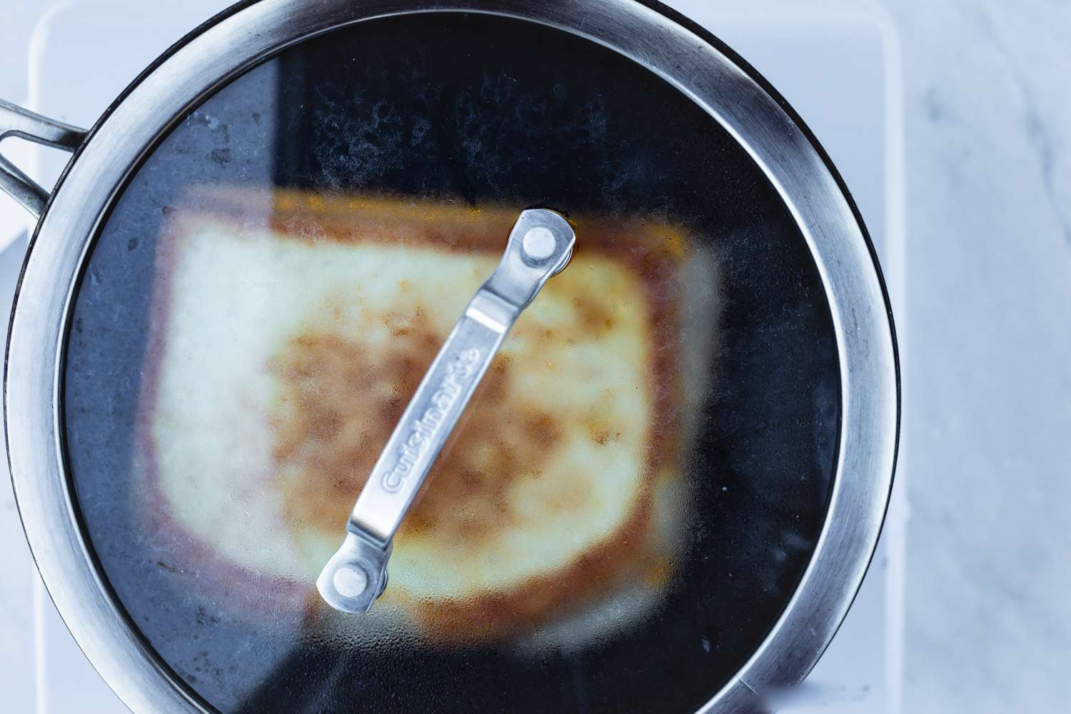 cooke grilled cheese in a covered skillet