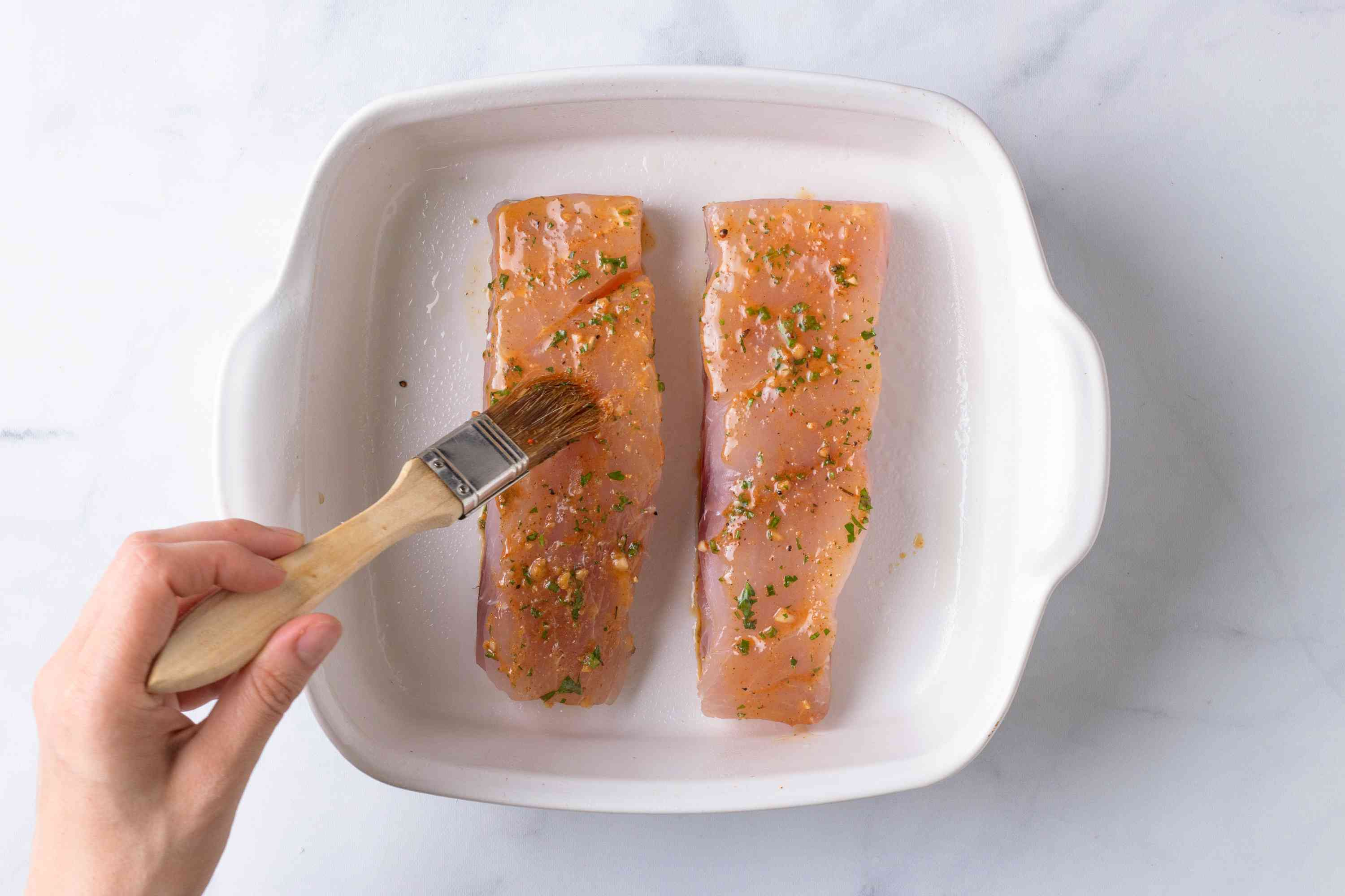 snapper fillets brushed with herb butter in a baking dish