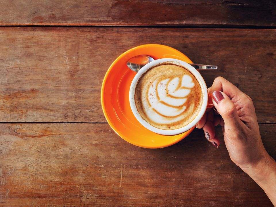 Close-Up Of Hand Holding Coffee Cup Over Table