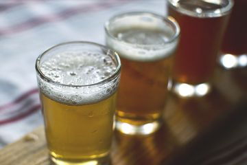 Beer in glasses by napkin on a wooden table