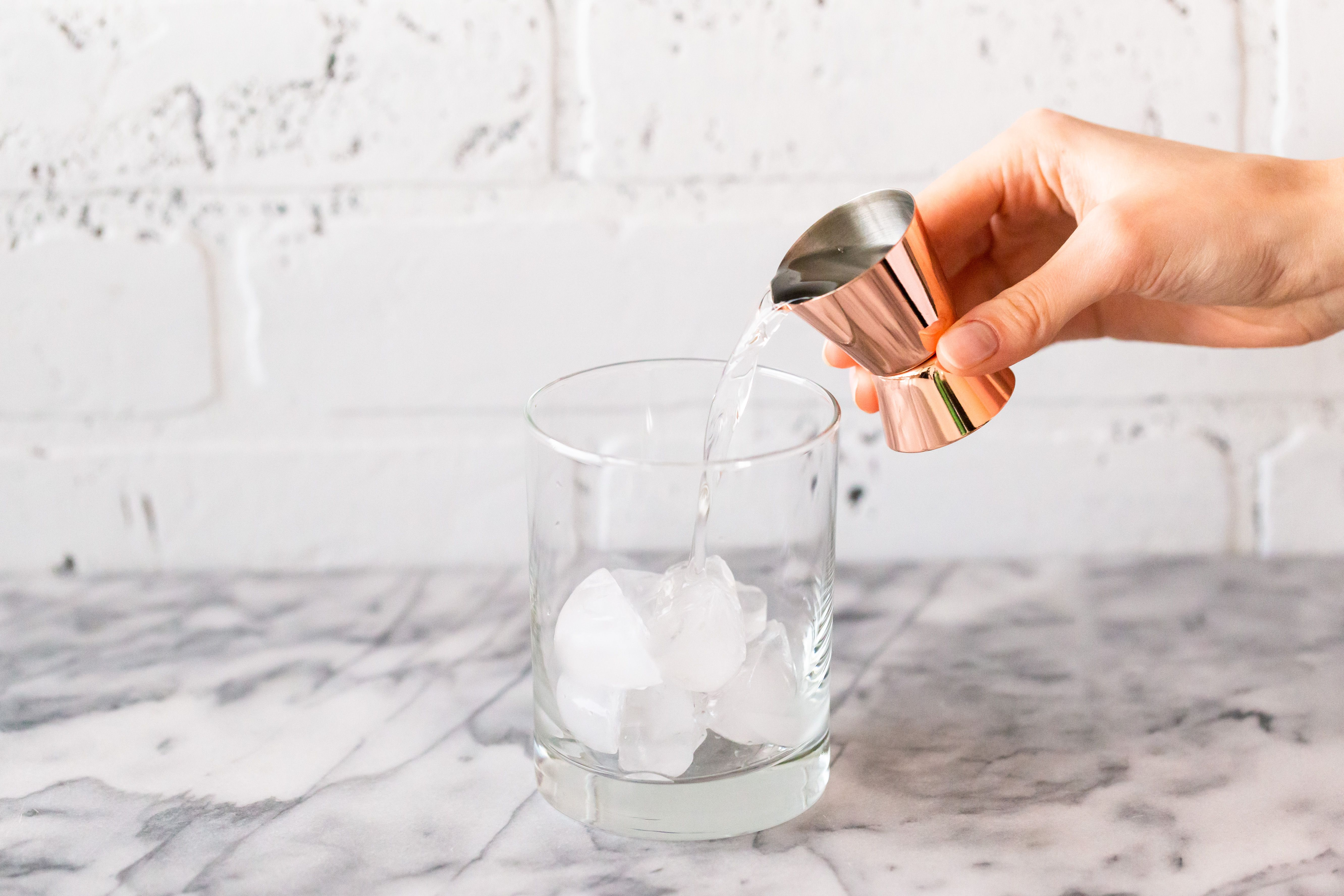 Vodka poured into a glass with ice