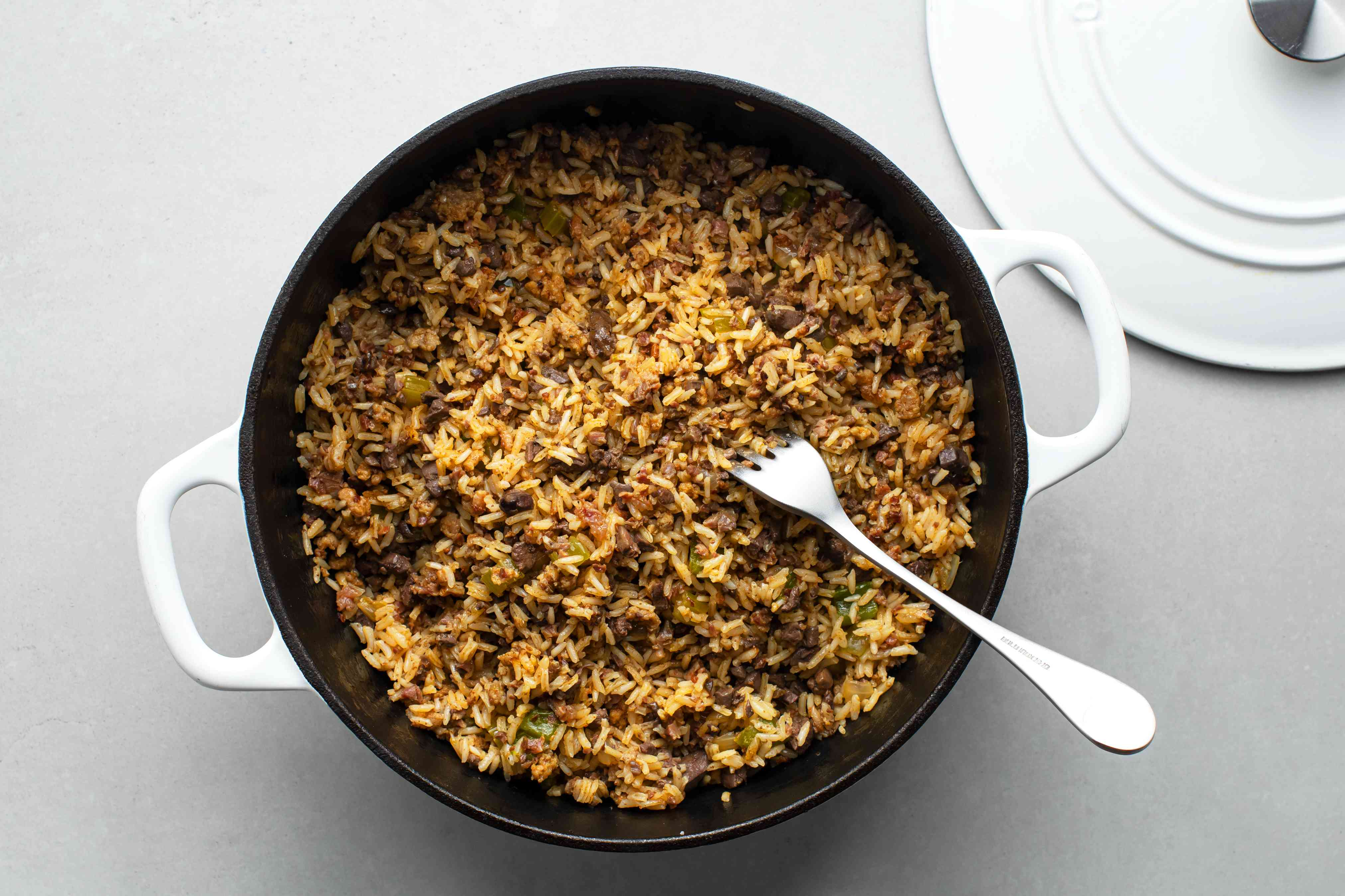 Fluff the Cajun dirty rice with a fork