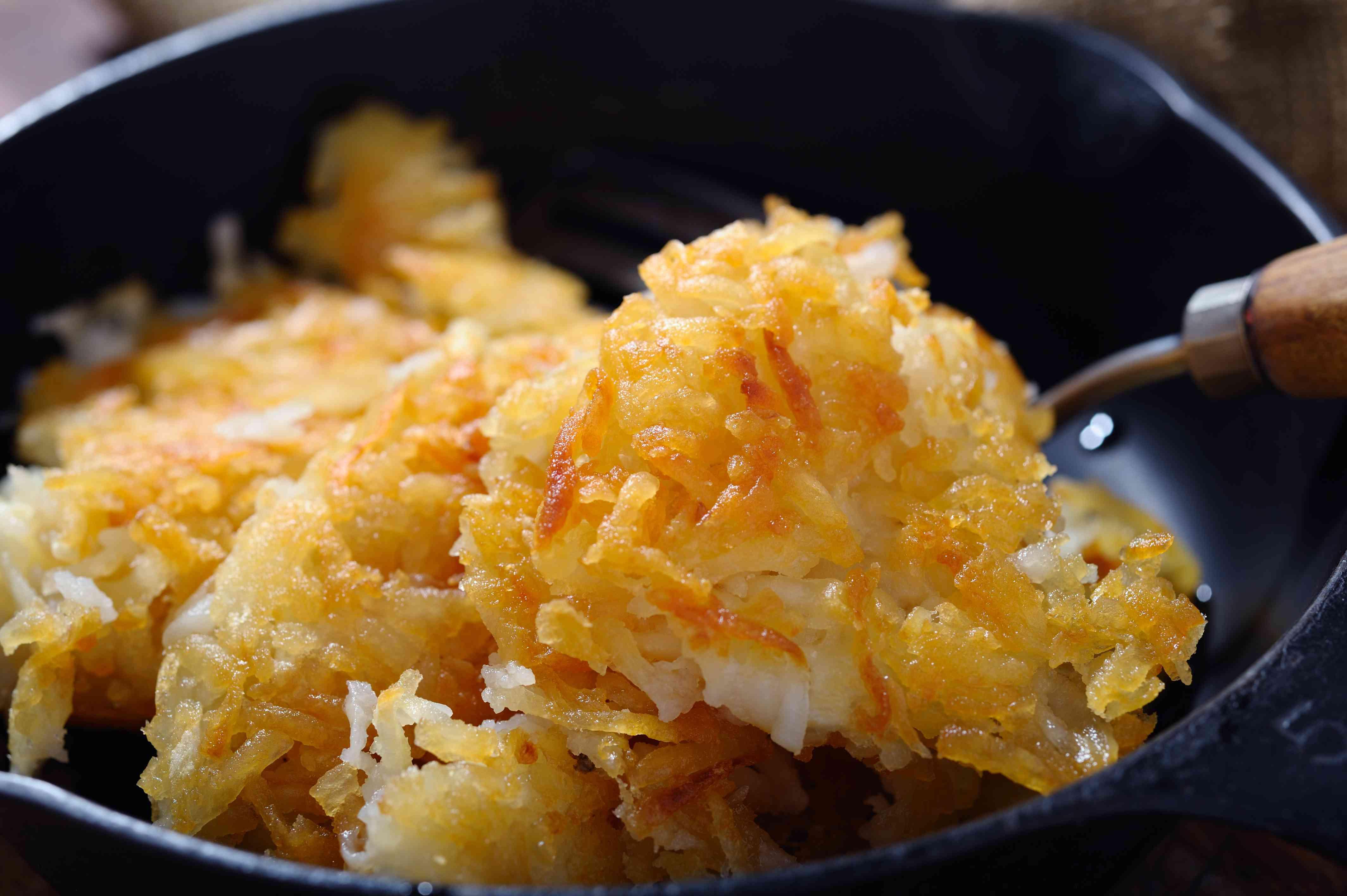 Golden hash browns in black frying pan