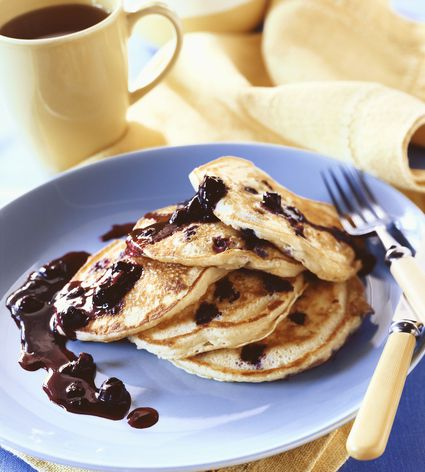 Stack of Blueberry Pancakes with Blueberry Sauce on a Blue Plate; Cup of Coffee