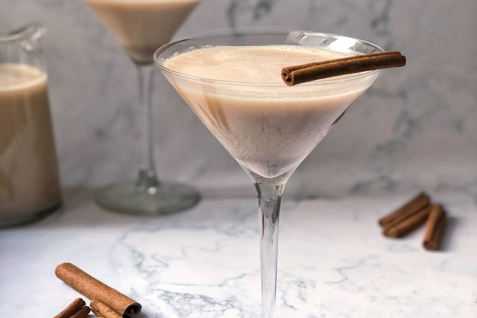 spiked horchata in a martini glass with stick of cinnamon as garnish