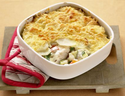 British fish pie in white bowl on wood board.