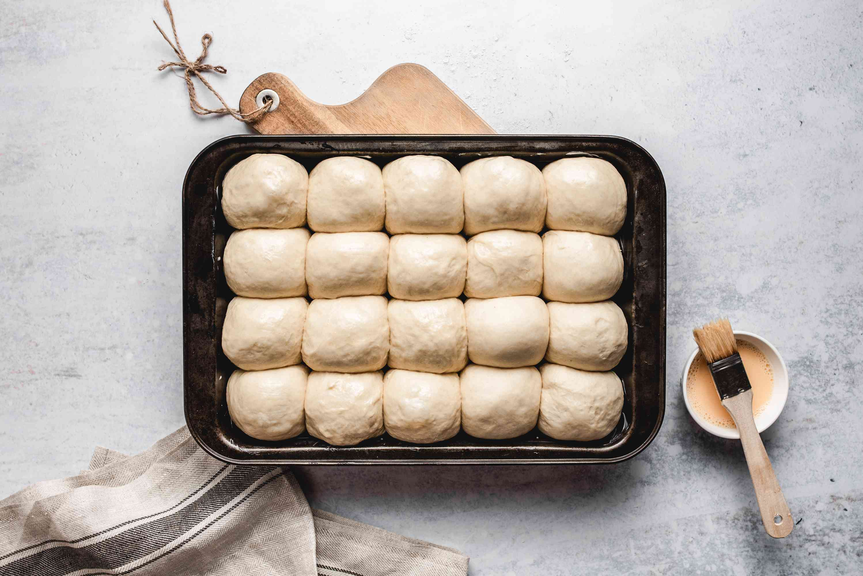 Dinner rolls unbaked in a baking sheet with an egg wash