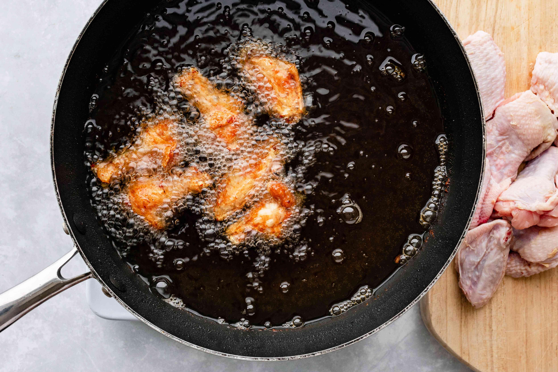 Buffalo wings frying in hot oil