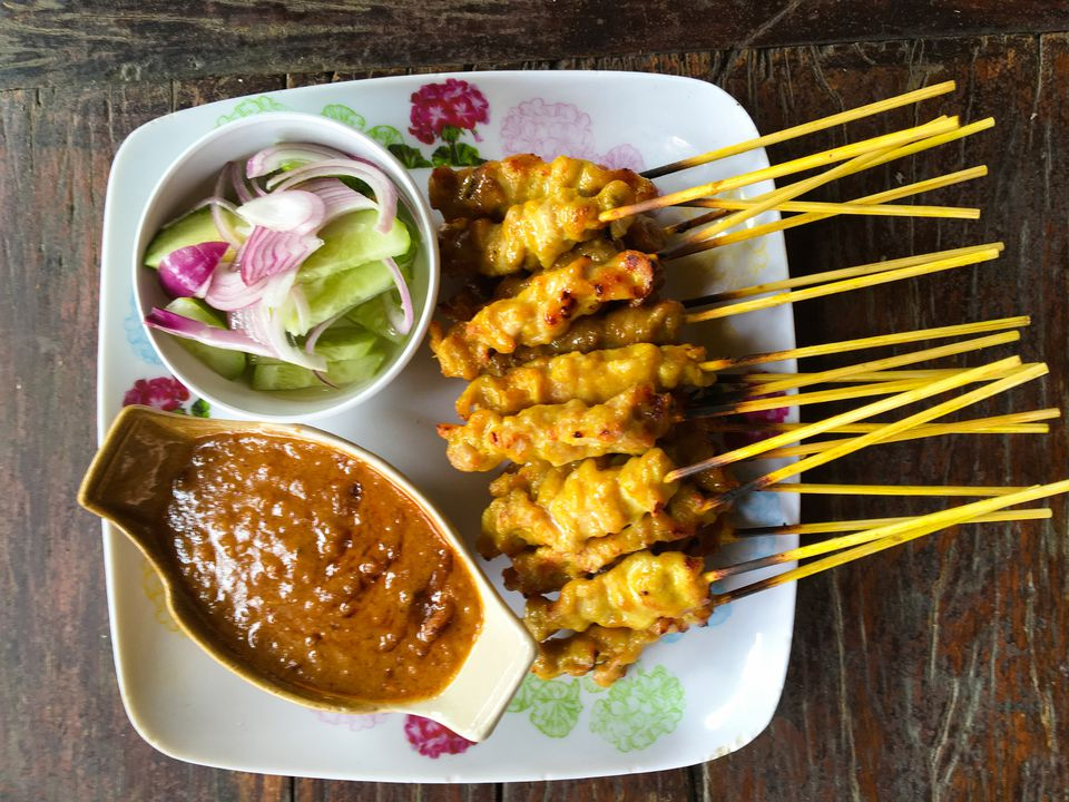 Chicken satay and salad with gravy in plate on table