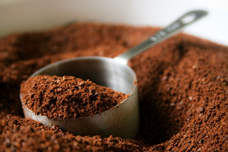 A measuring cup in a pile of coffee grounds