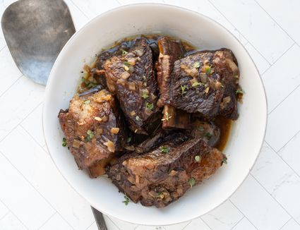 serving bowl with beef short ribs braised in the oven