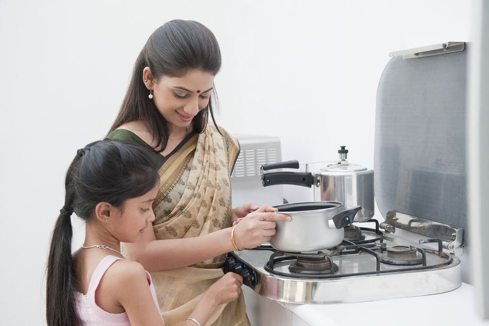 Indian mom and daughter using pressure cooker