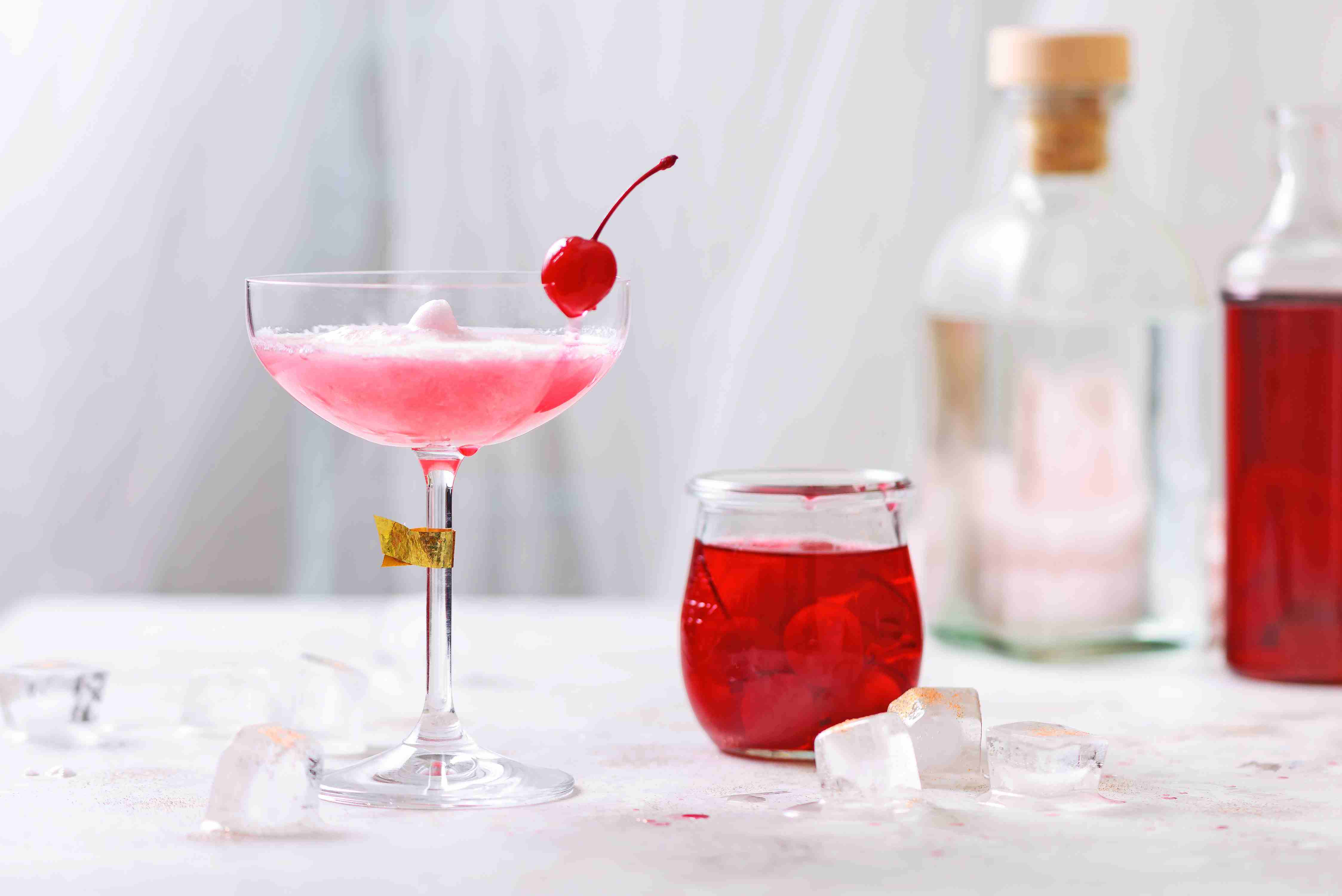 Pink lady cocktail garnished with a maraschino cherry