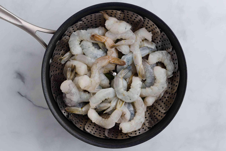 shrimp in a steamer basket in a saucepan