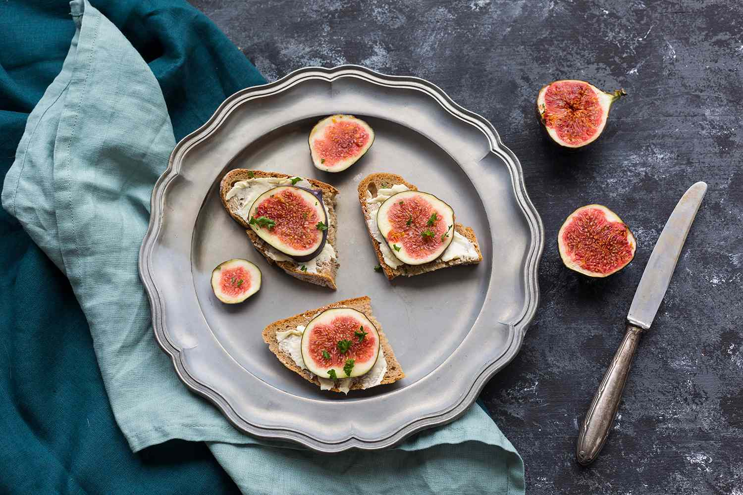 Buttered slices of bread with sliced figs on tin plate