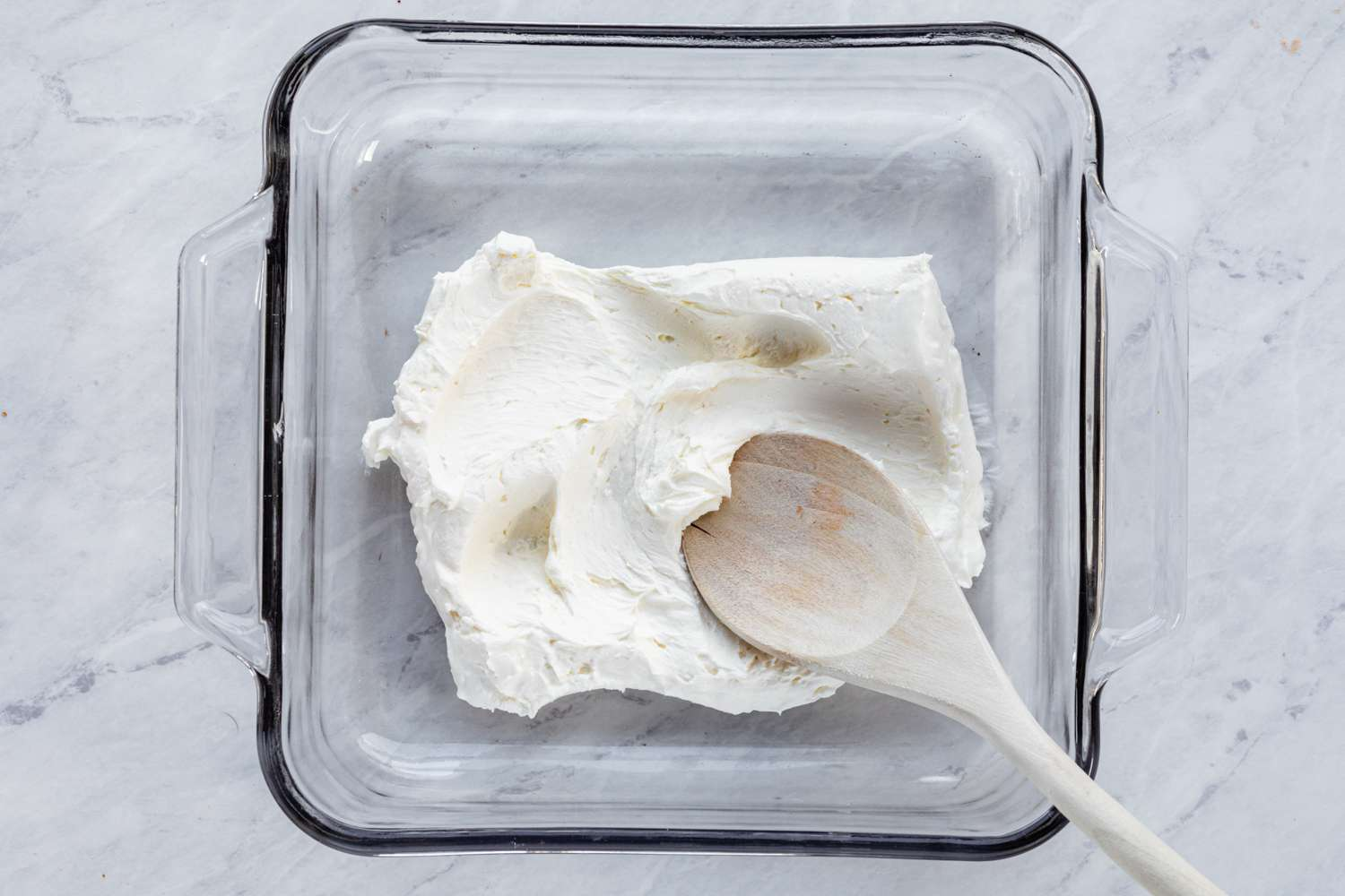 Place softened cream cheese into a deep baking dish