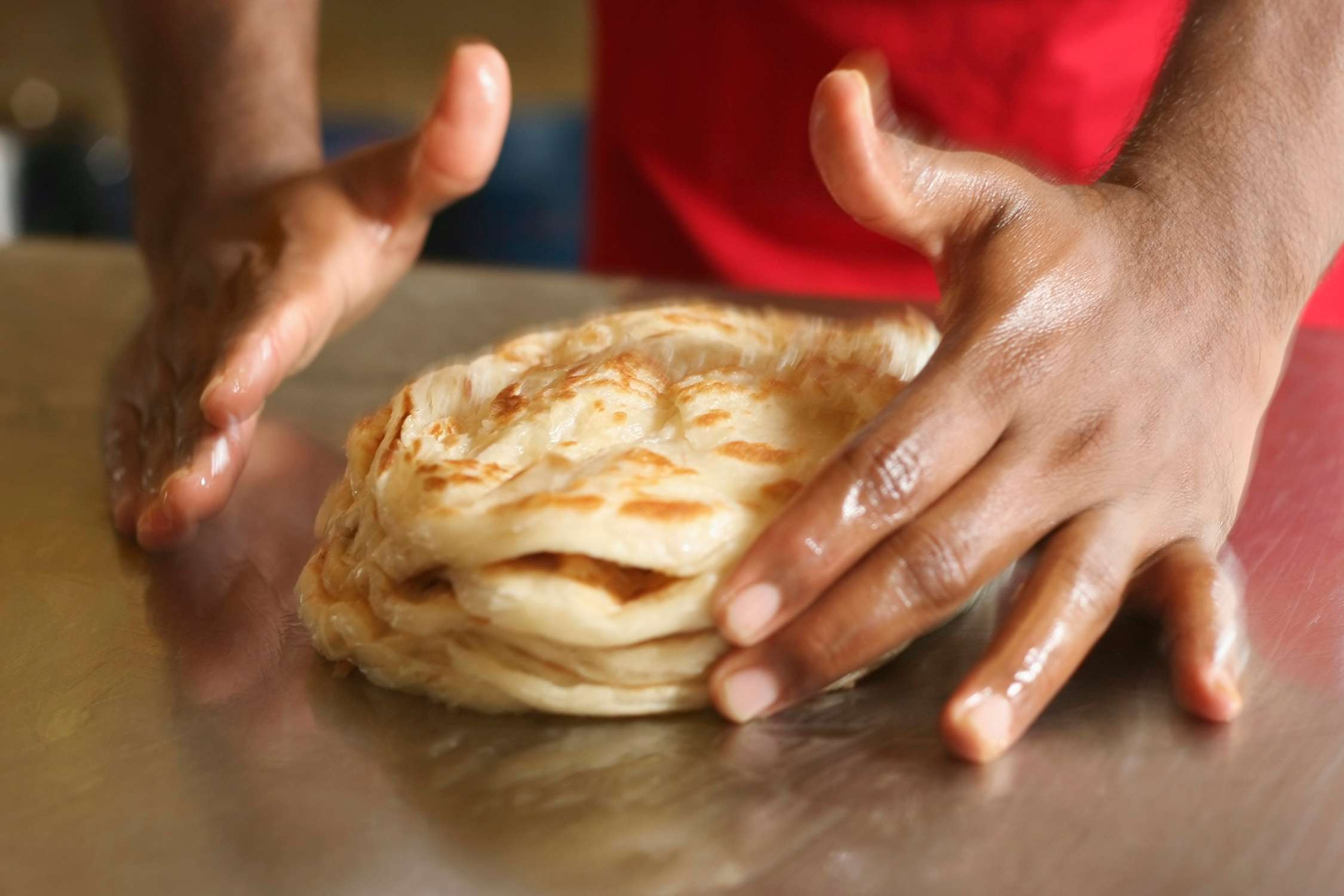 Giving the roti canai a whack to fluff it up